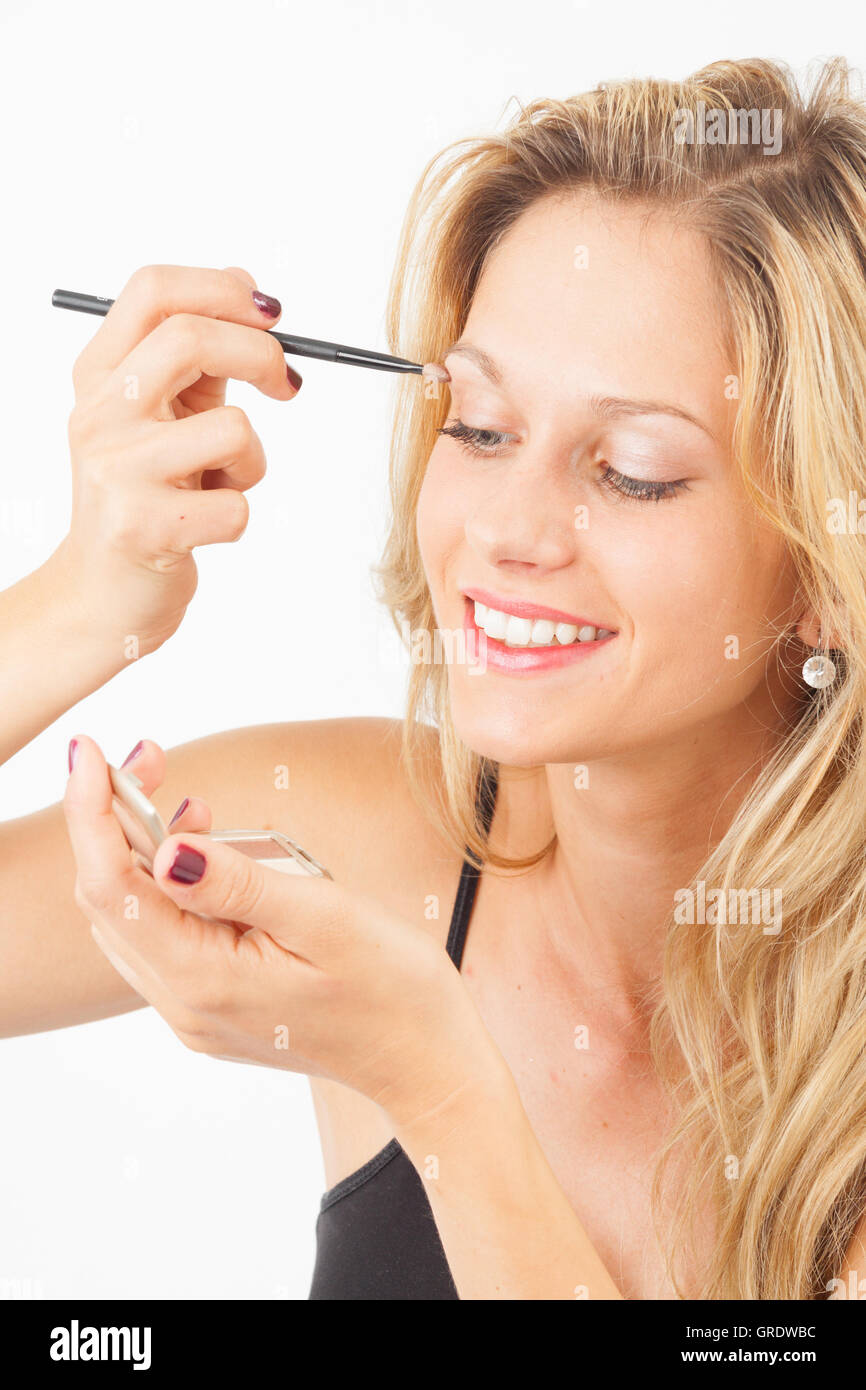 Young Woman Putting Eyeshadow On With A Spatula Stock Photo