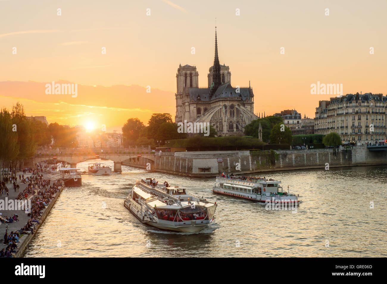 Notre Dame de Paris cathedral with cruise ship in Seine river in Paris, France. Beautiful sunset in Paris, France - Stock Image