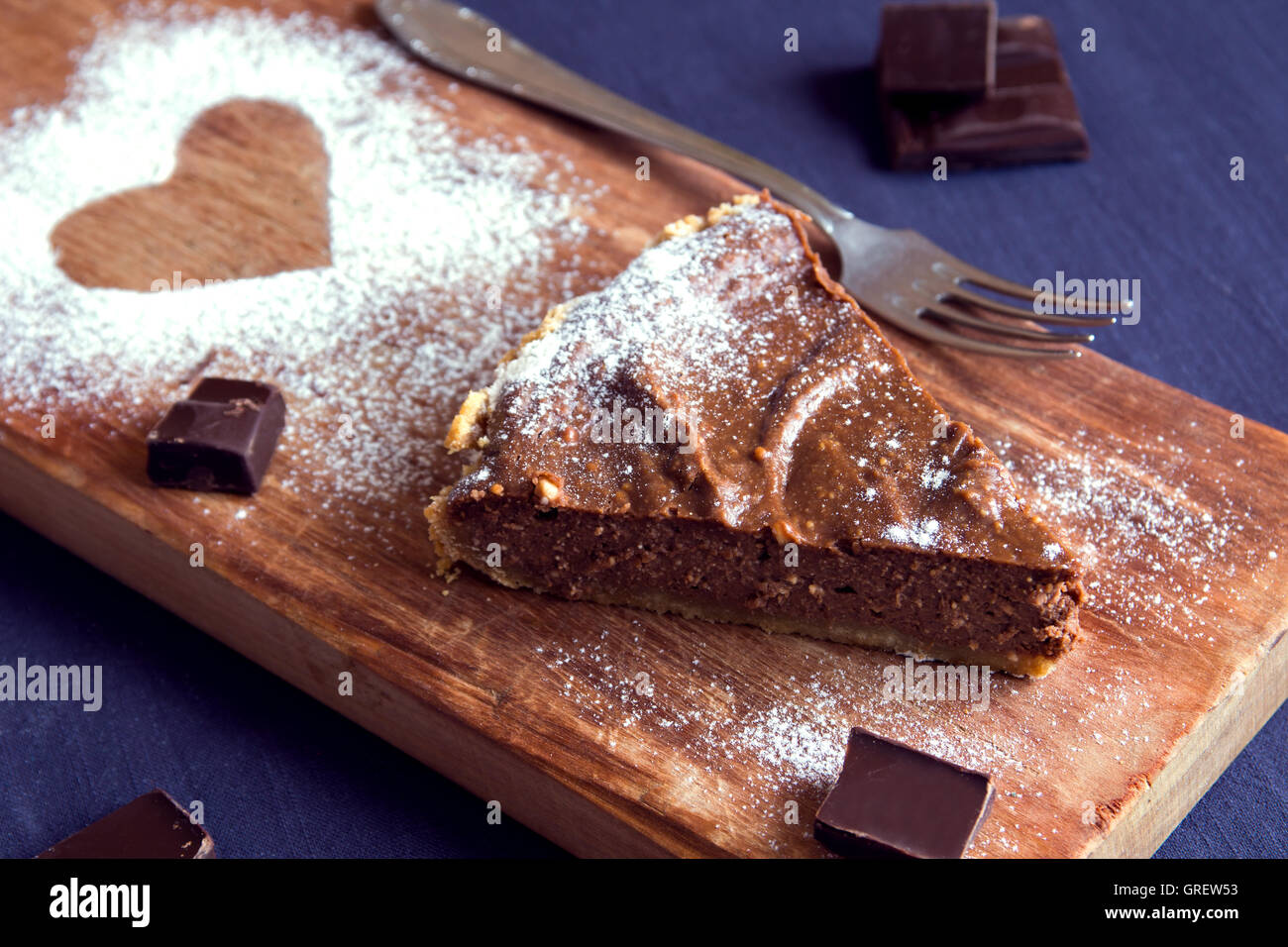 Homemade chocolate cheesecake (pie) on wooden board with heart shape sugar powder (dessert with love) - Stock Image