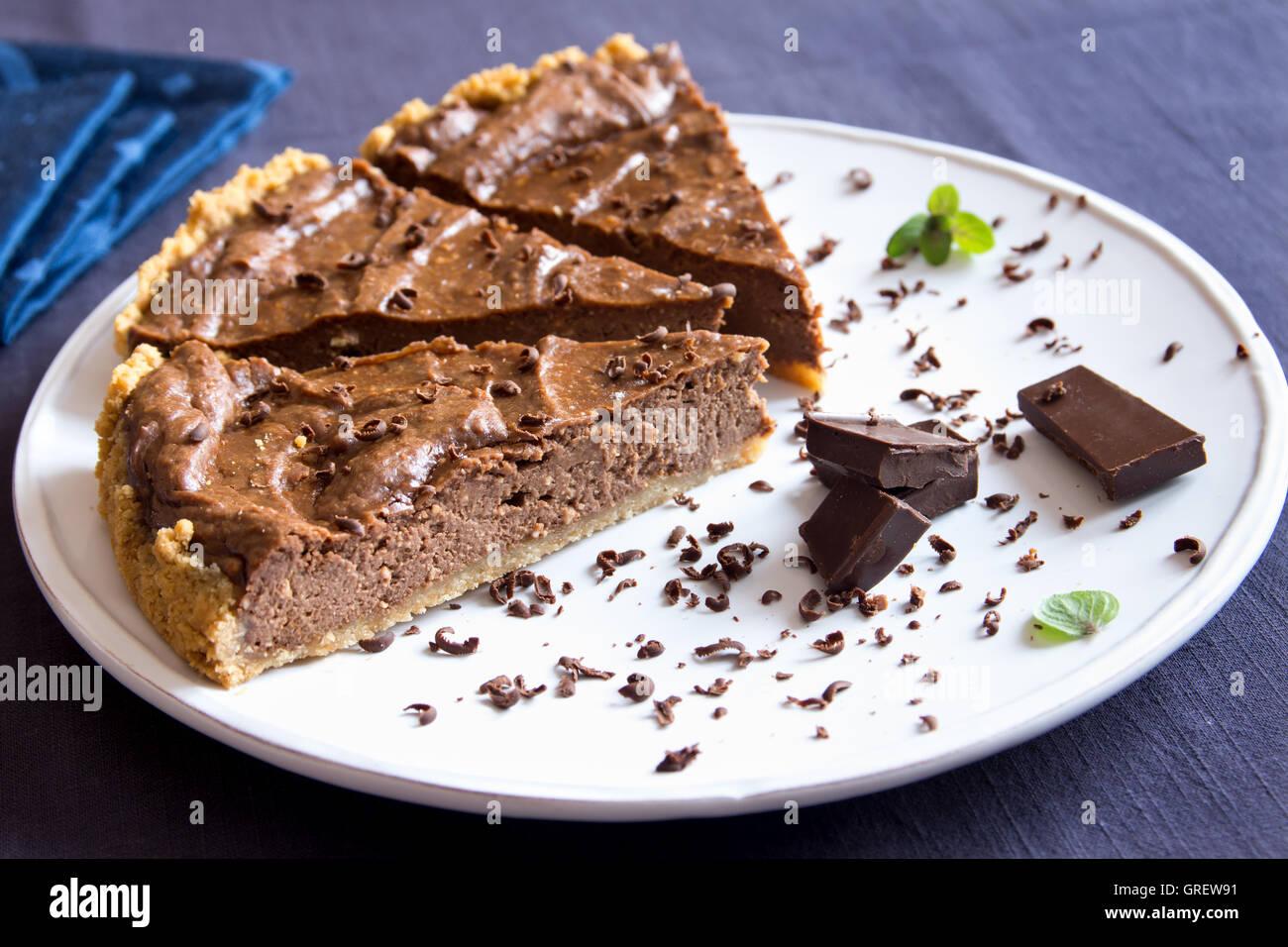 Homemade chocolate pie (cheesecake) on white plate close up - Stock Image