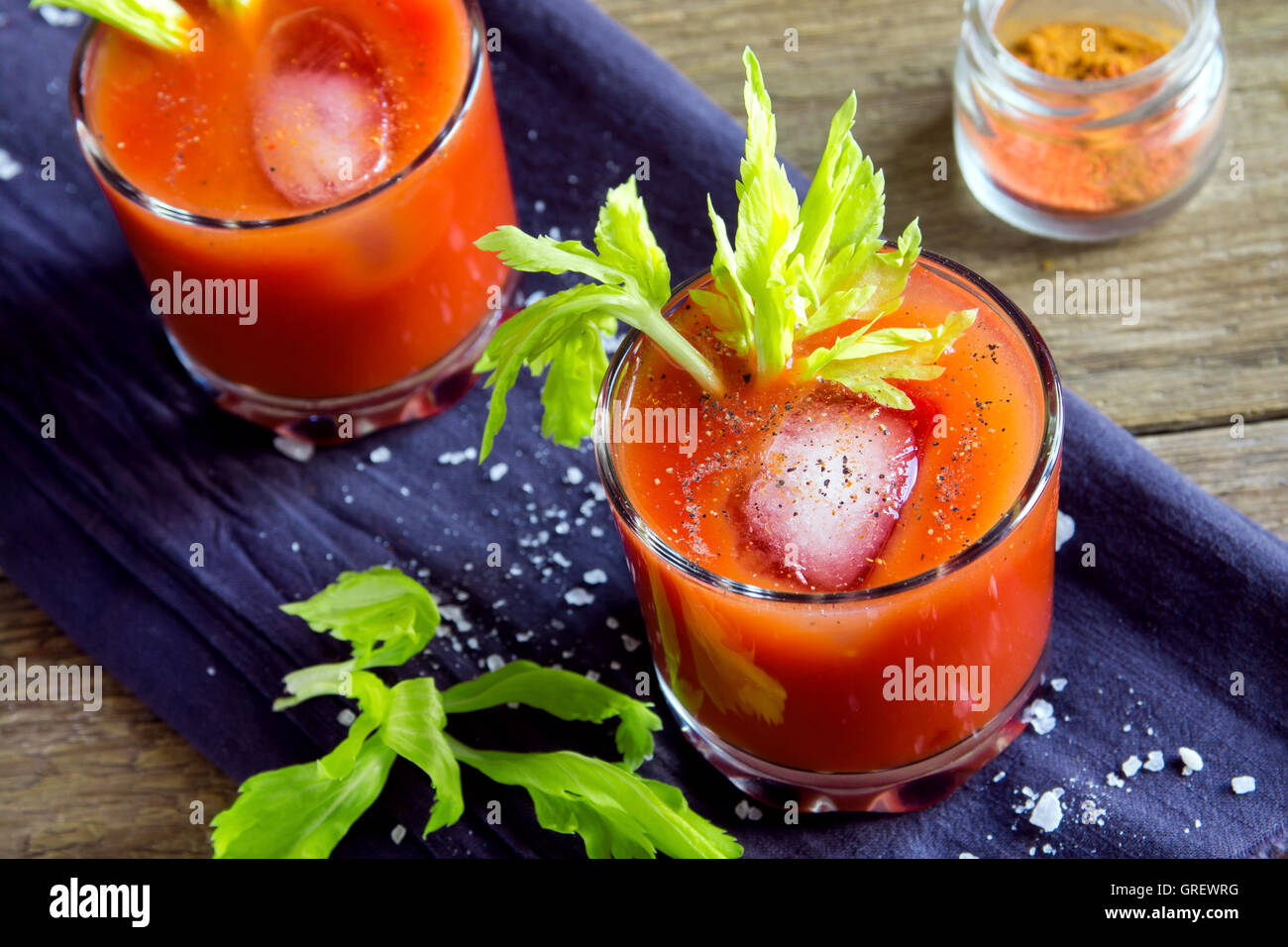 Tomato juice with celery, spices, salt and ice in portion glasses - Stock Image