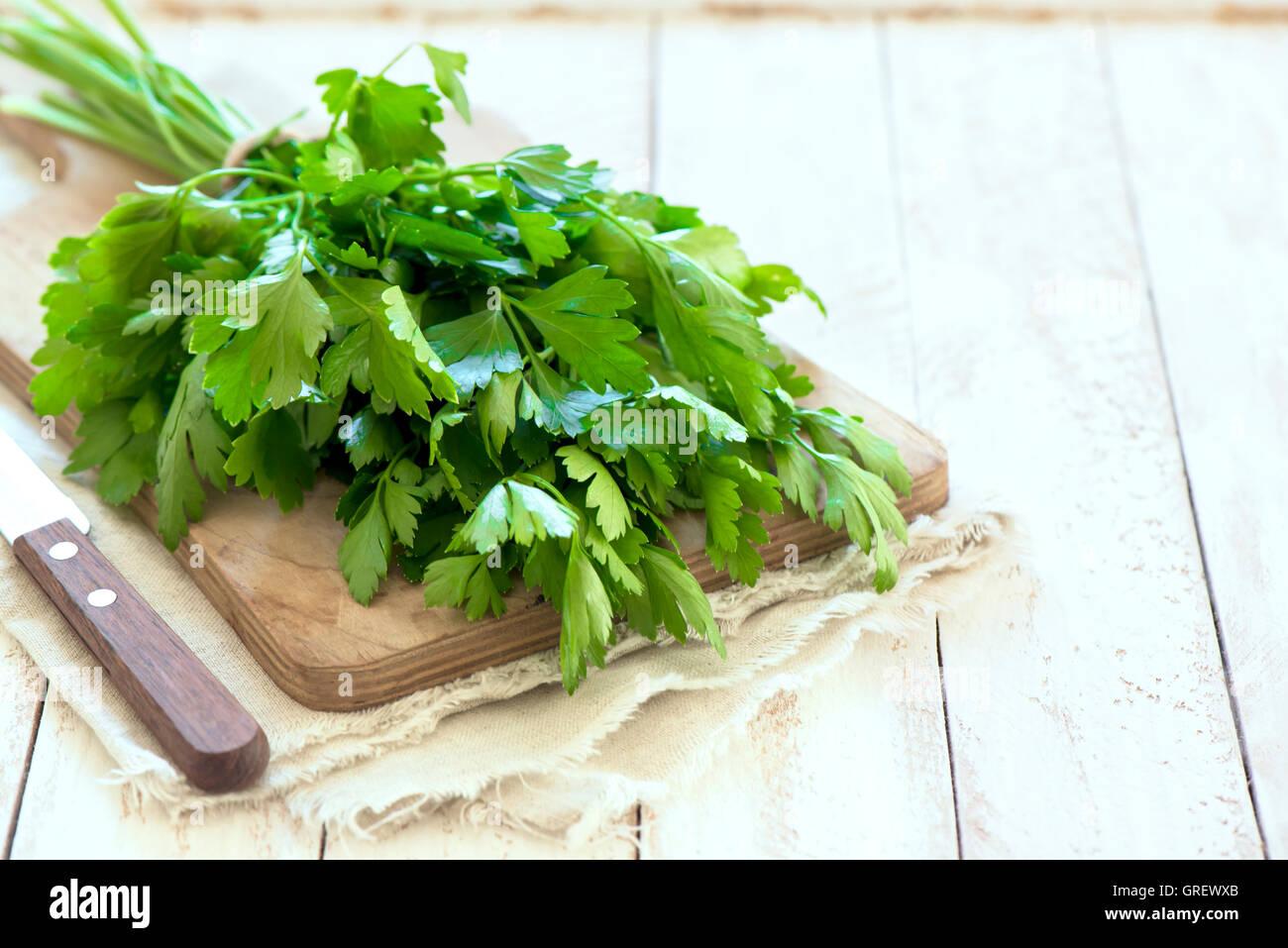 Organic italian parsley closeup on rustic wooden table, healthy vegetarian food - Stock Image