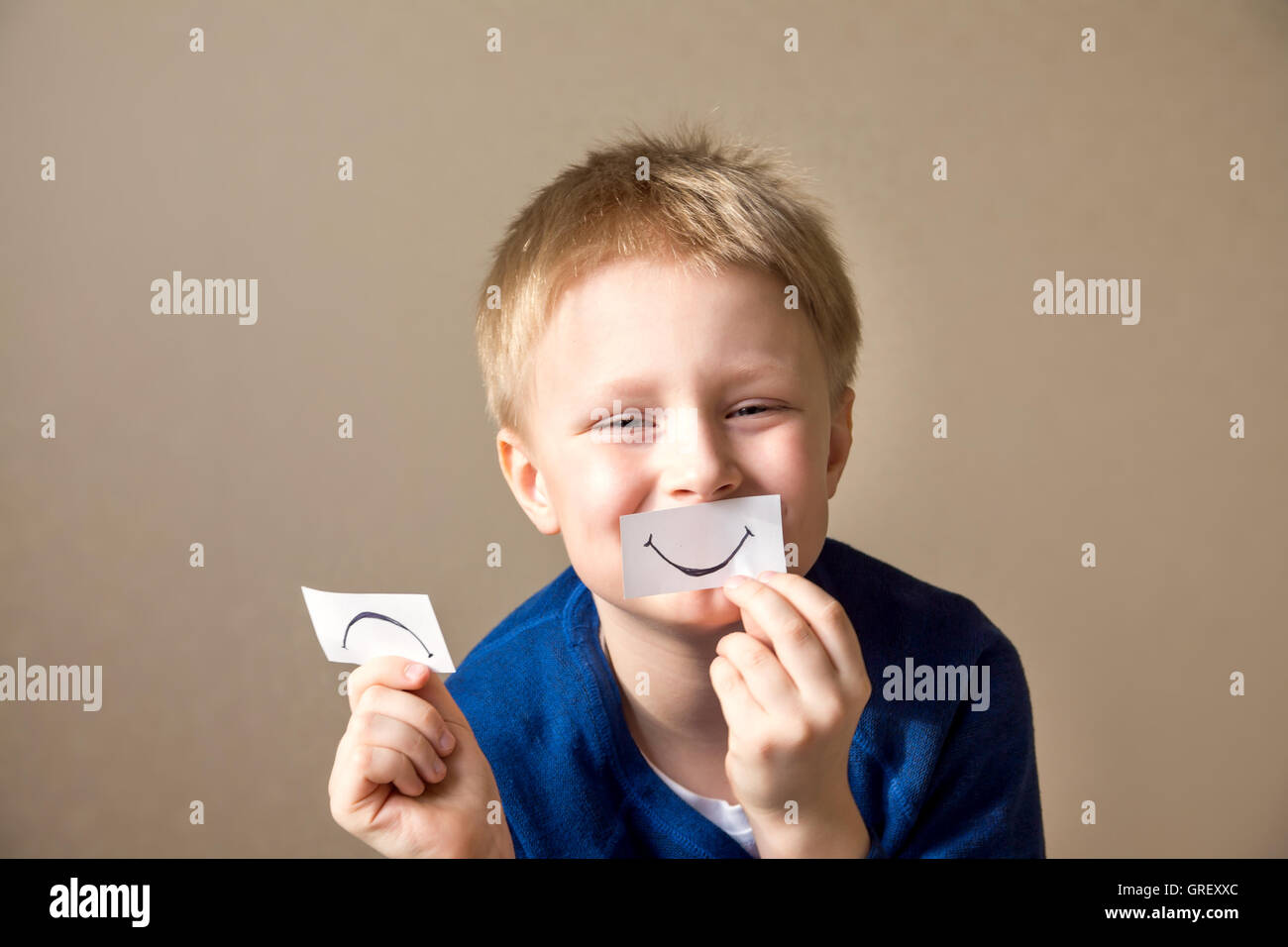 Young boy (teen) select between positive and negative expressions - Stock Image