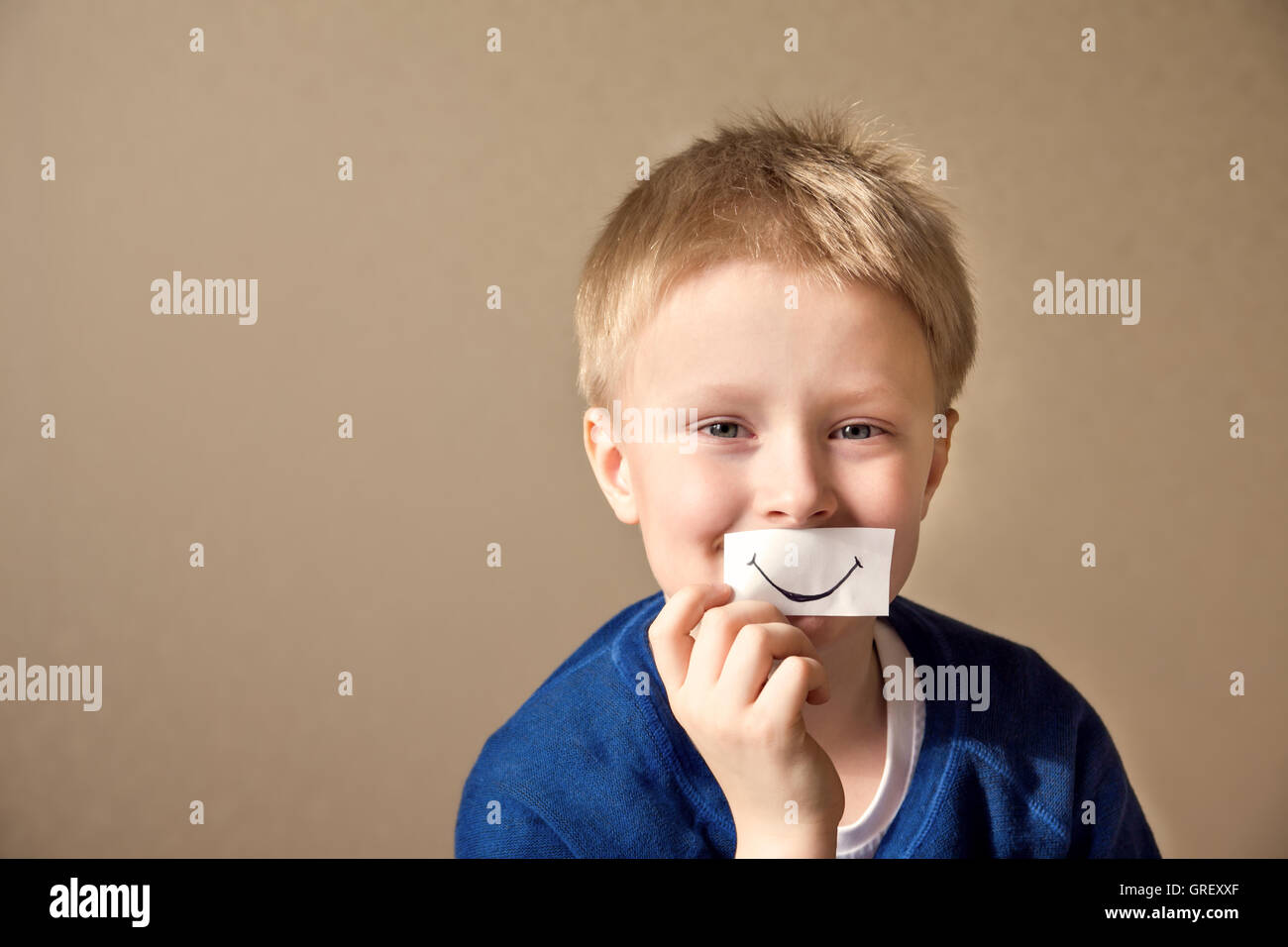 Happy young boy (teen) with paper smile select right positive expressions - Stock Image