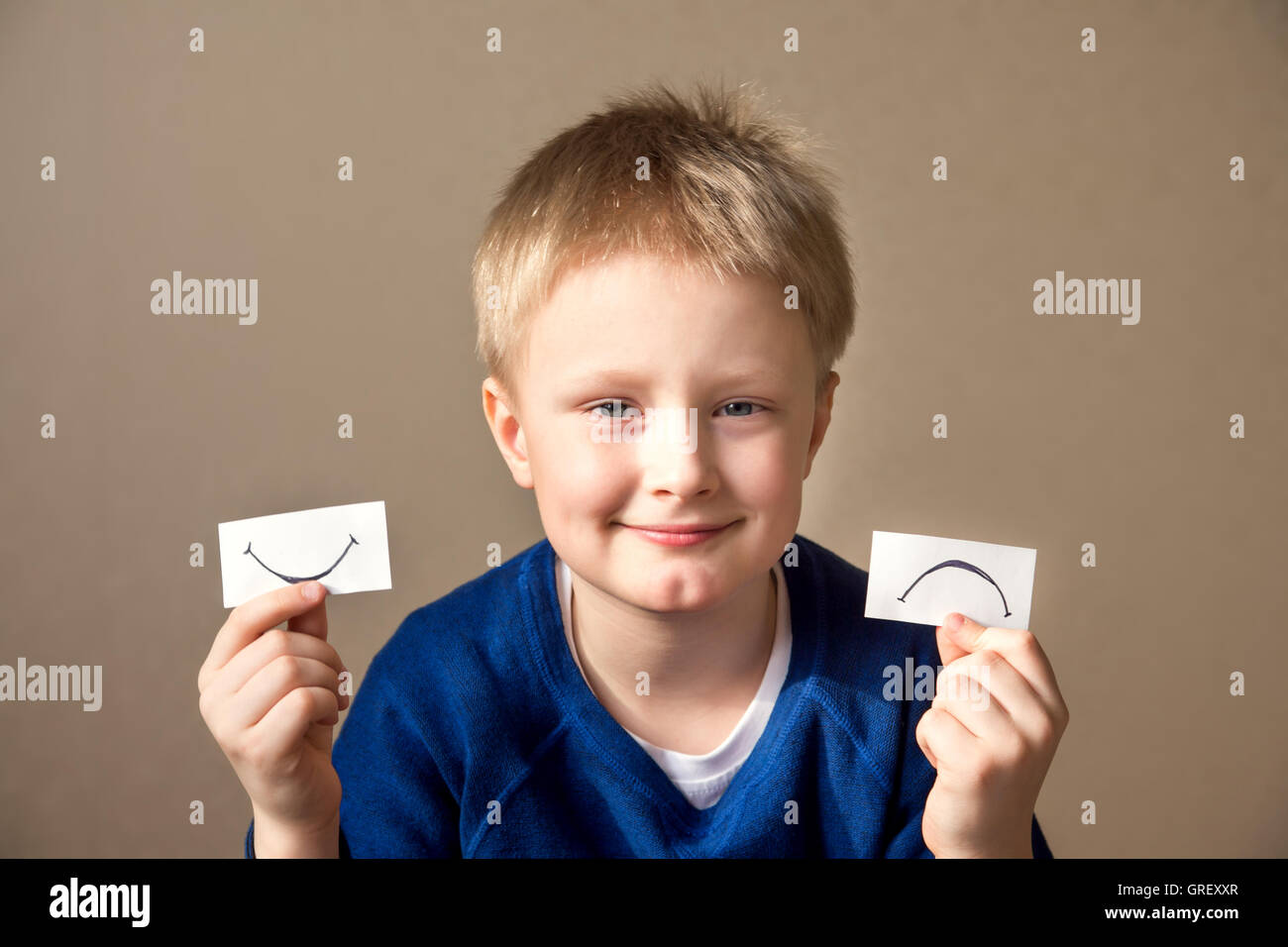 Young boy select between positive and negative expressions - Stock Image
