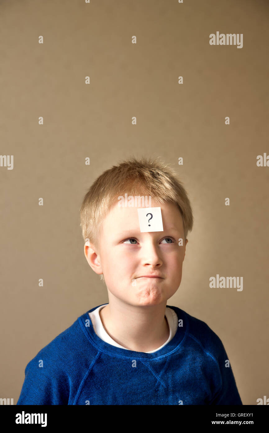 thinking confused young boy (teen) with question mark on gray background - Stock Image