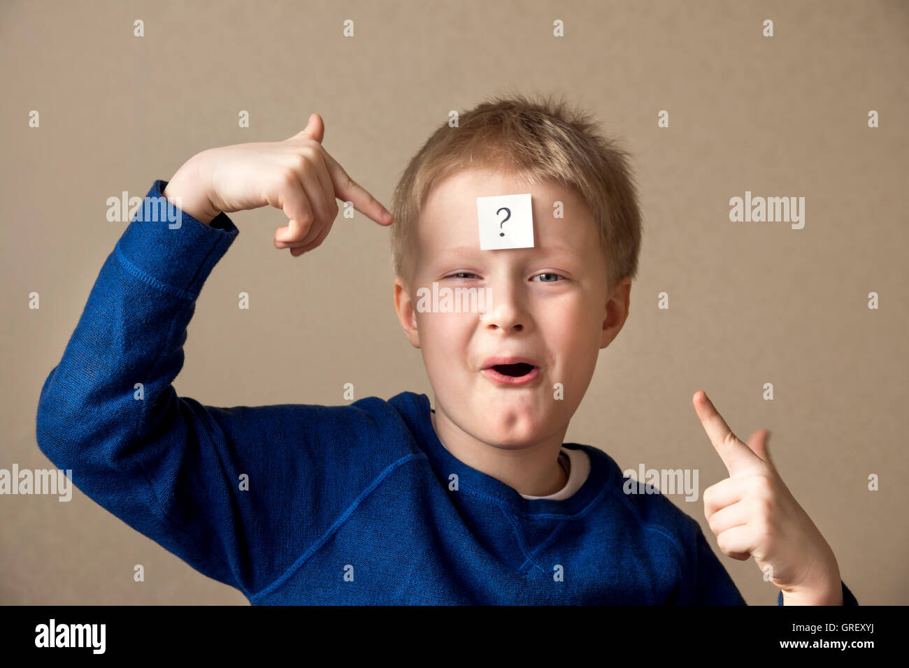 thinking young boy with question mark on gray background - Stock Image