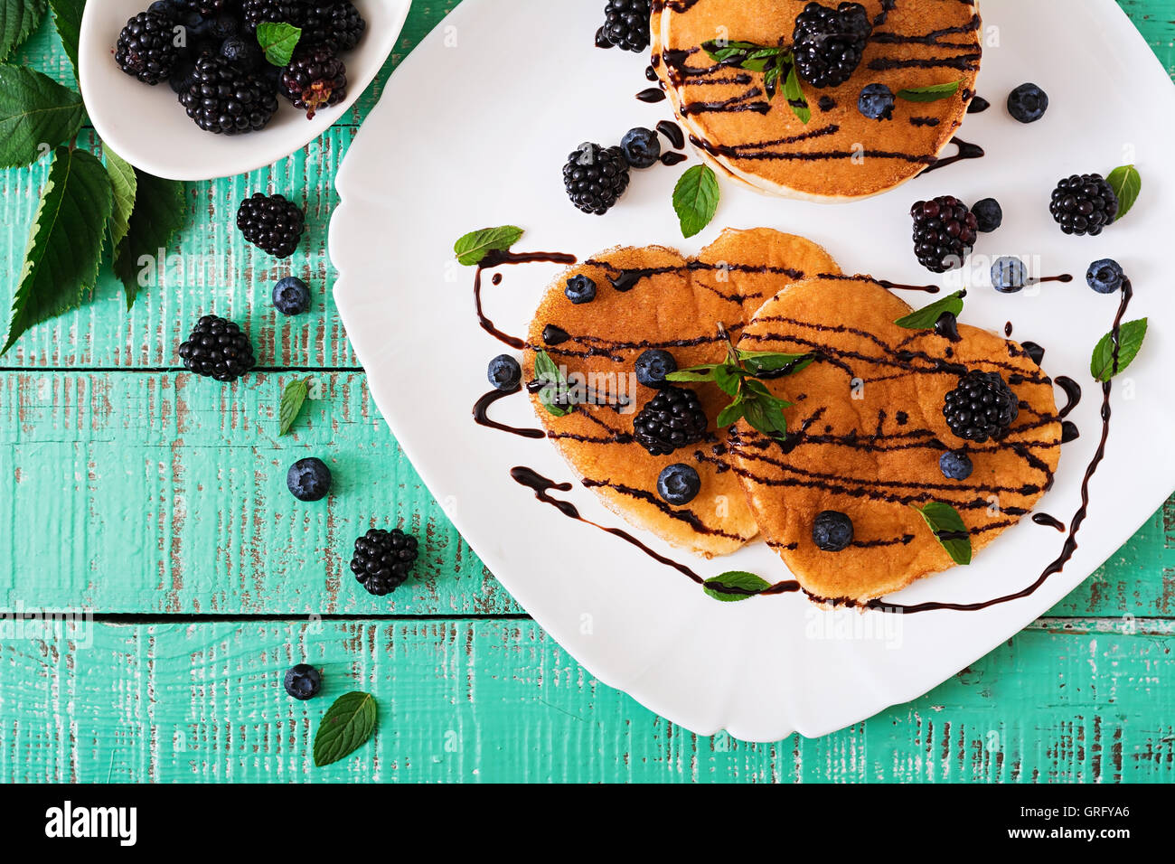 Delicious pancakes with blackberries and chocolate. Top view - Stock Image