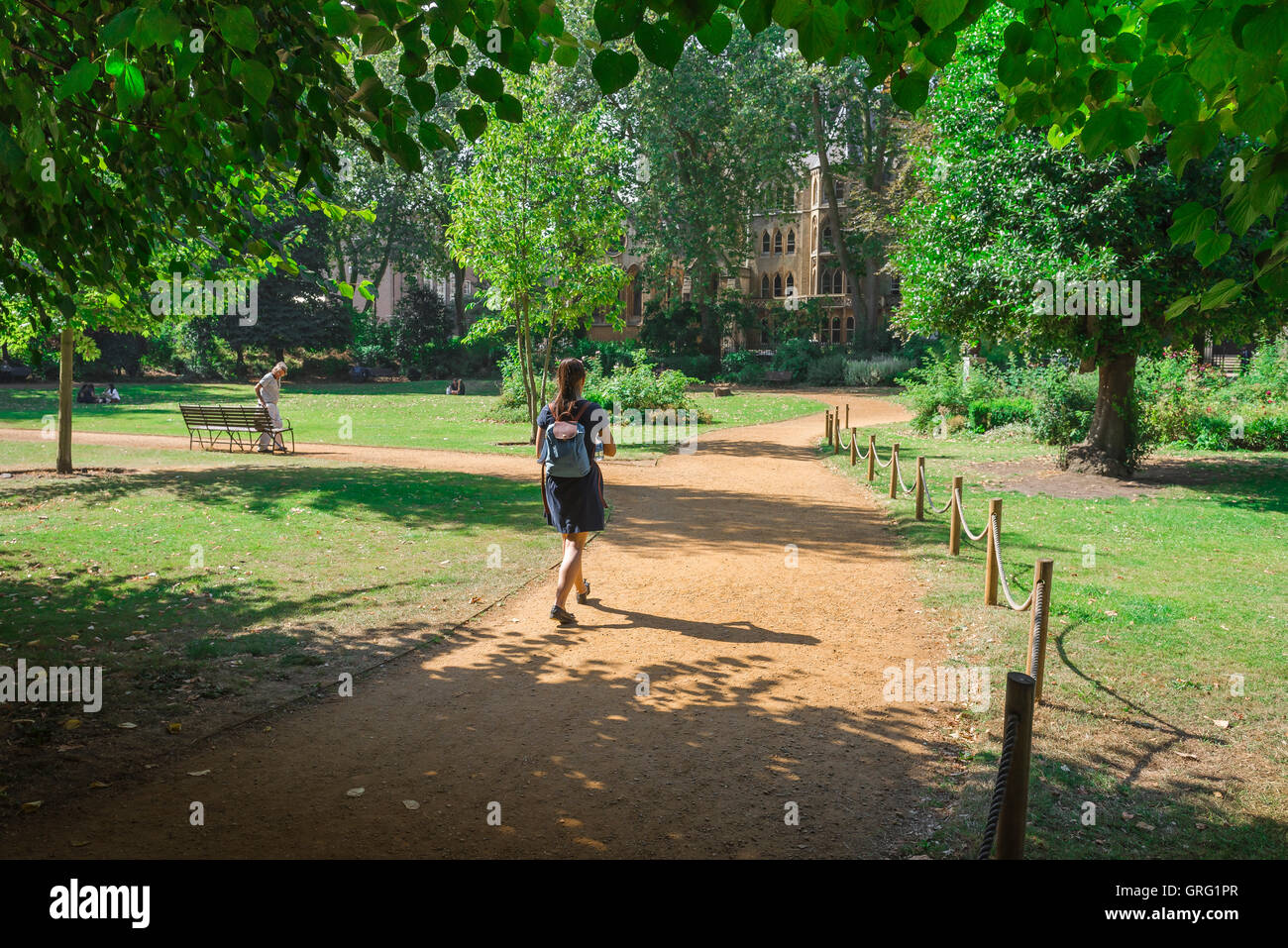 London park, rear view of a young woman wearing a backpack walking through Gordon Square in Bloomsbury on a summer - Stock Image