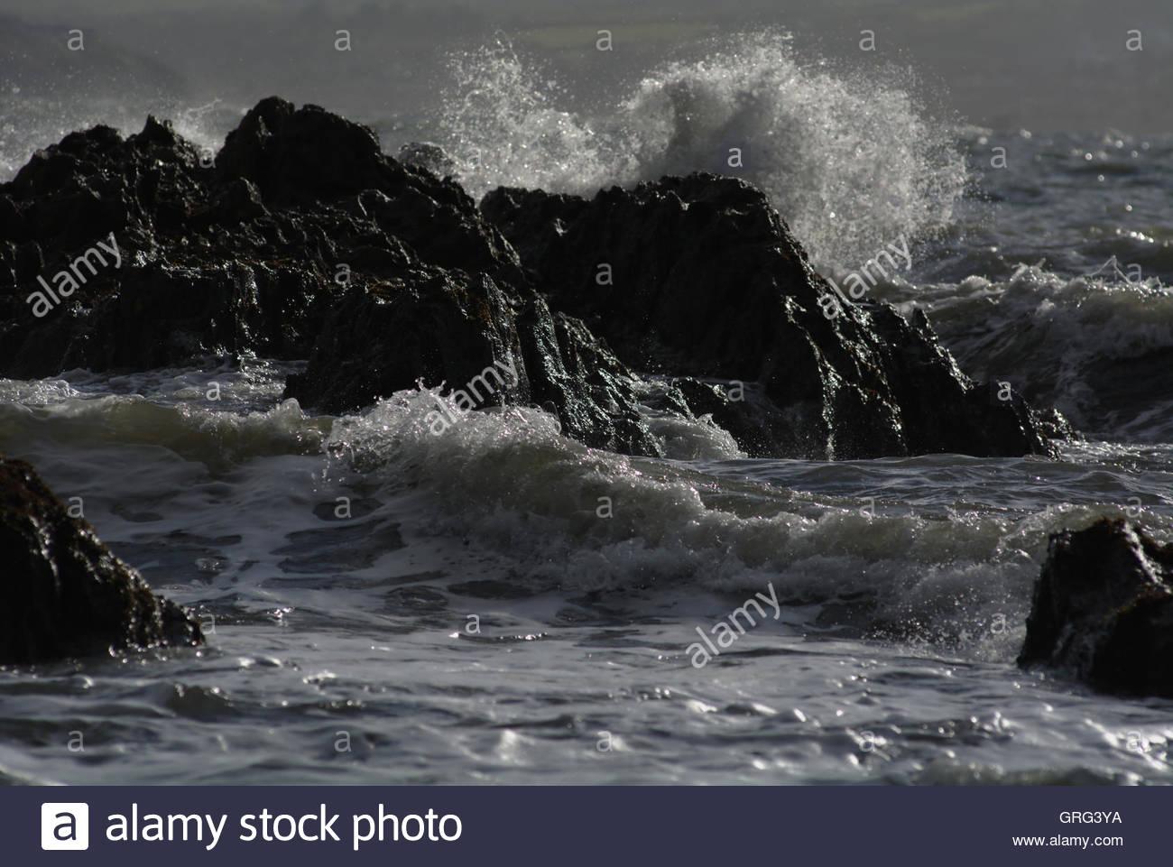 Storm waves smashing against rocks - Stock Image