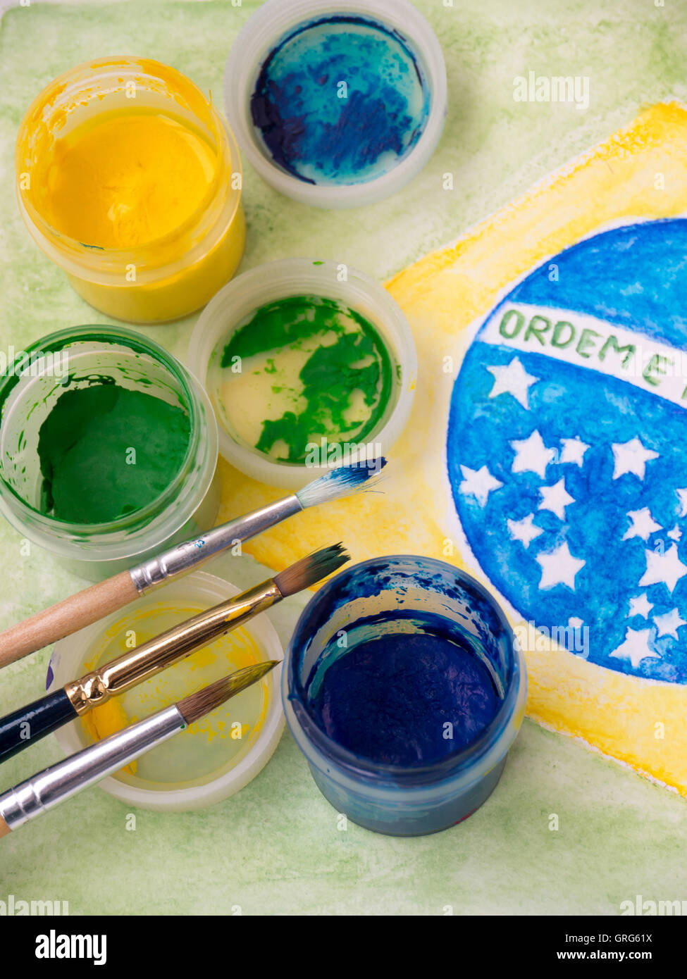Paint in jars, lids and brushes on the brazil flag watercolor painting.  Inscription on the flag 'Ordem e Progresso' - Stock Image