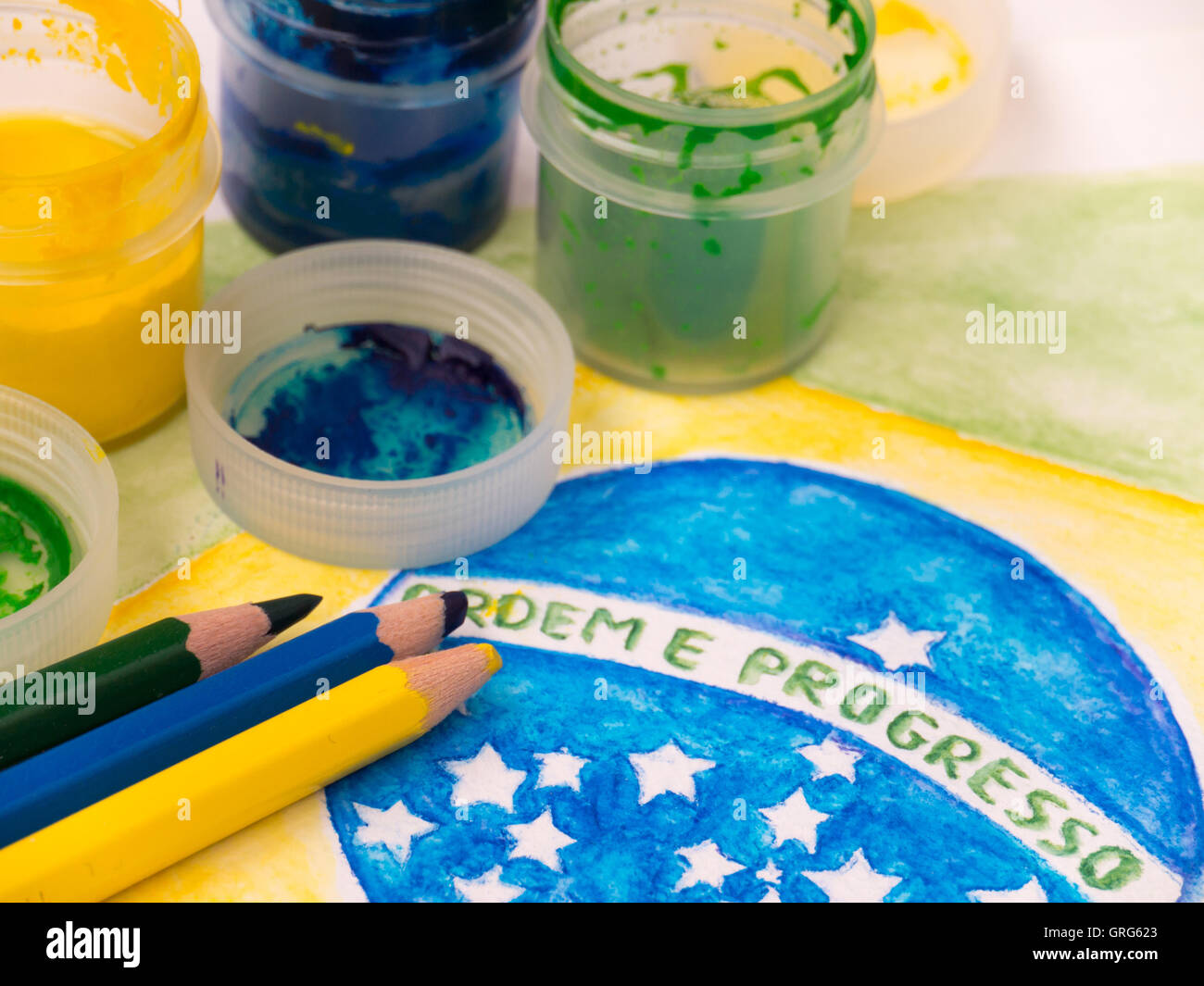 Paint in jars, lids and pencils on the brazil flag watercolor painting.  Inscription on the flag 'Ordem e Progresso' - Stock Image