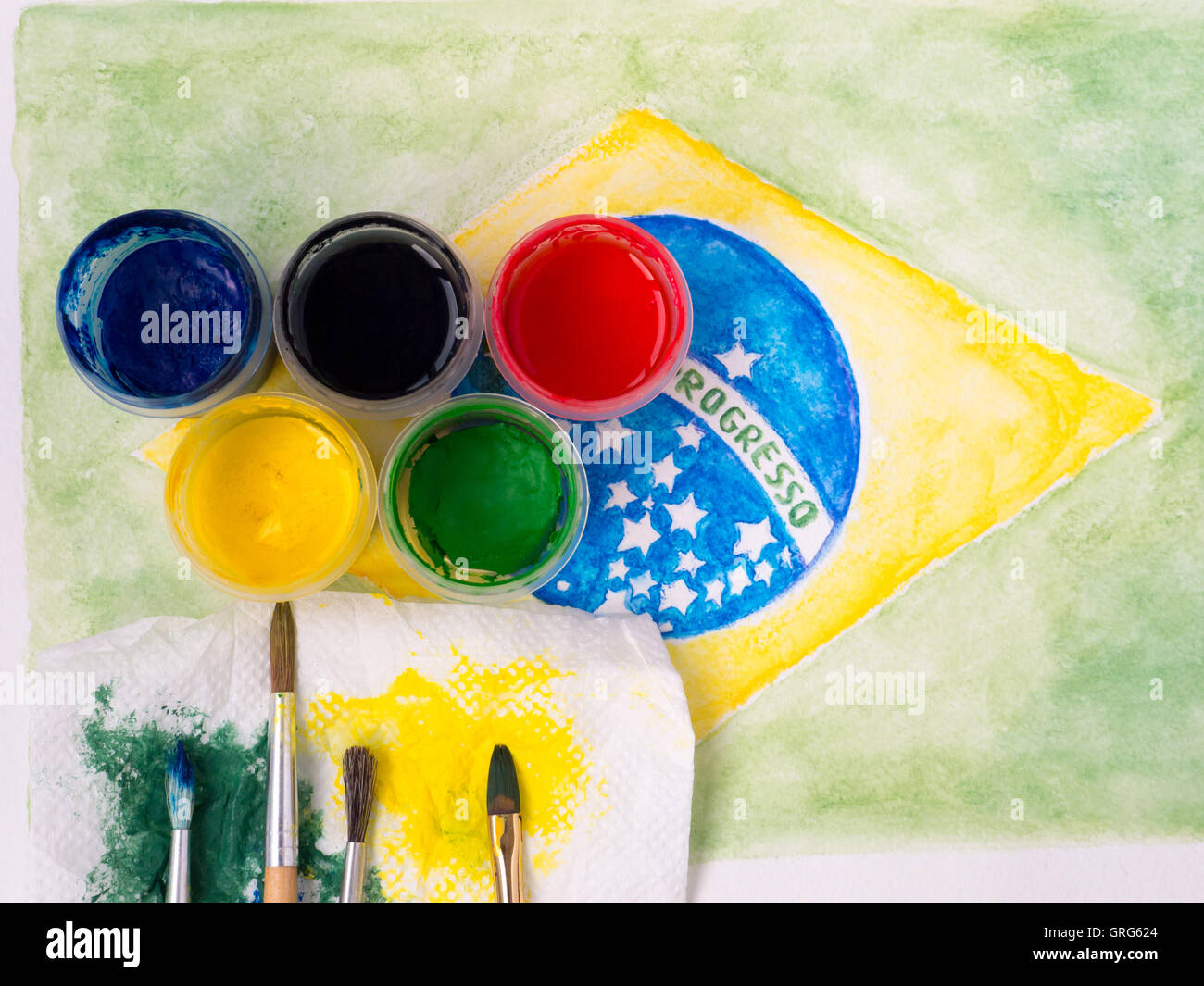 Paints,brushes and and stained with paints fabric on the brazil flag watercolor painting Motto on the flag 'Ordem - Stock Image