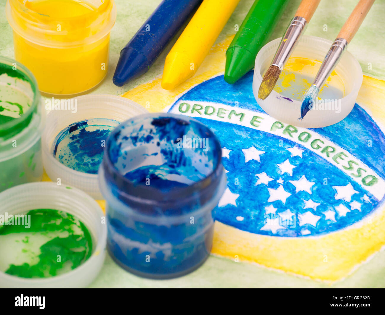 Paint in jars,lids,brushes and crayons on the brazil flag watercolor painting.  Motto on the flag 'Ordem e Progresso' - Stock Image