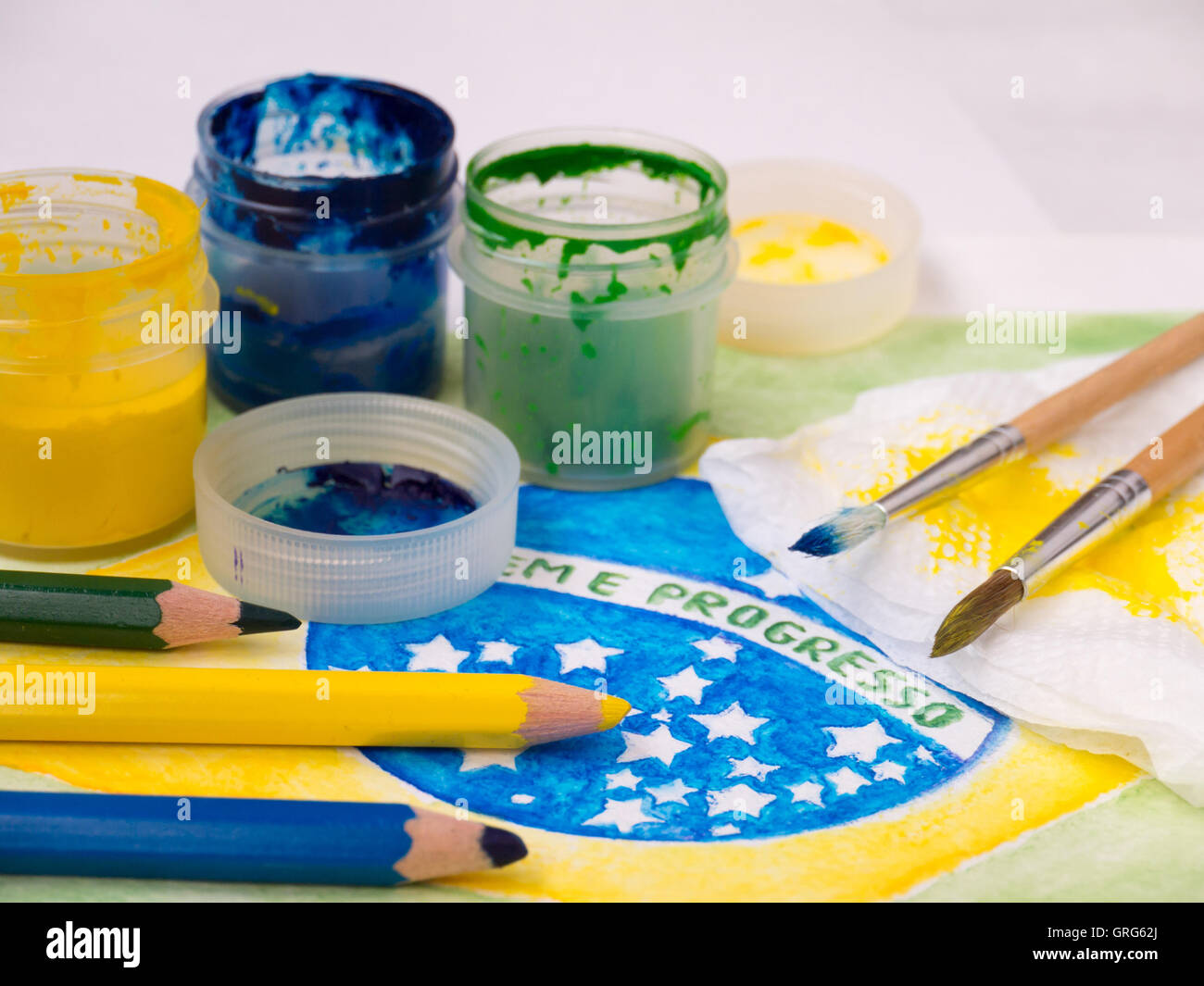 Paint in jars,lids,brushes and pencils on the brazil flag watercolor painting.  Motto on the flag 'Ordem e Progresso' - Stock Image