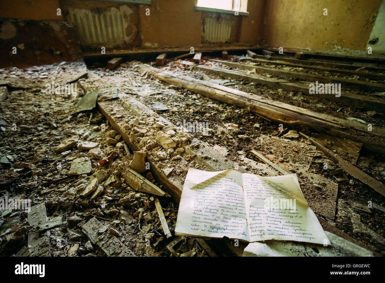 The Consequences Of The Nuclear Pollution After Chernobyl Disaster. The Pupil's Copybook On The Ruined Floor - Stock Image