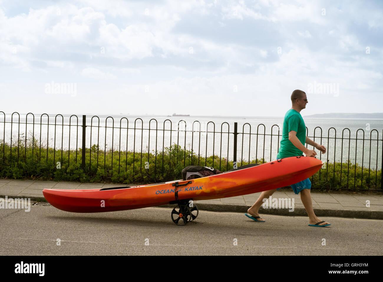 Falmouth, UK. 8th September, 2016. Man pulling his kayak on a trailer to Gyllyngvase Beach, Falmouth Credit:  Mick - Stock Image