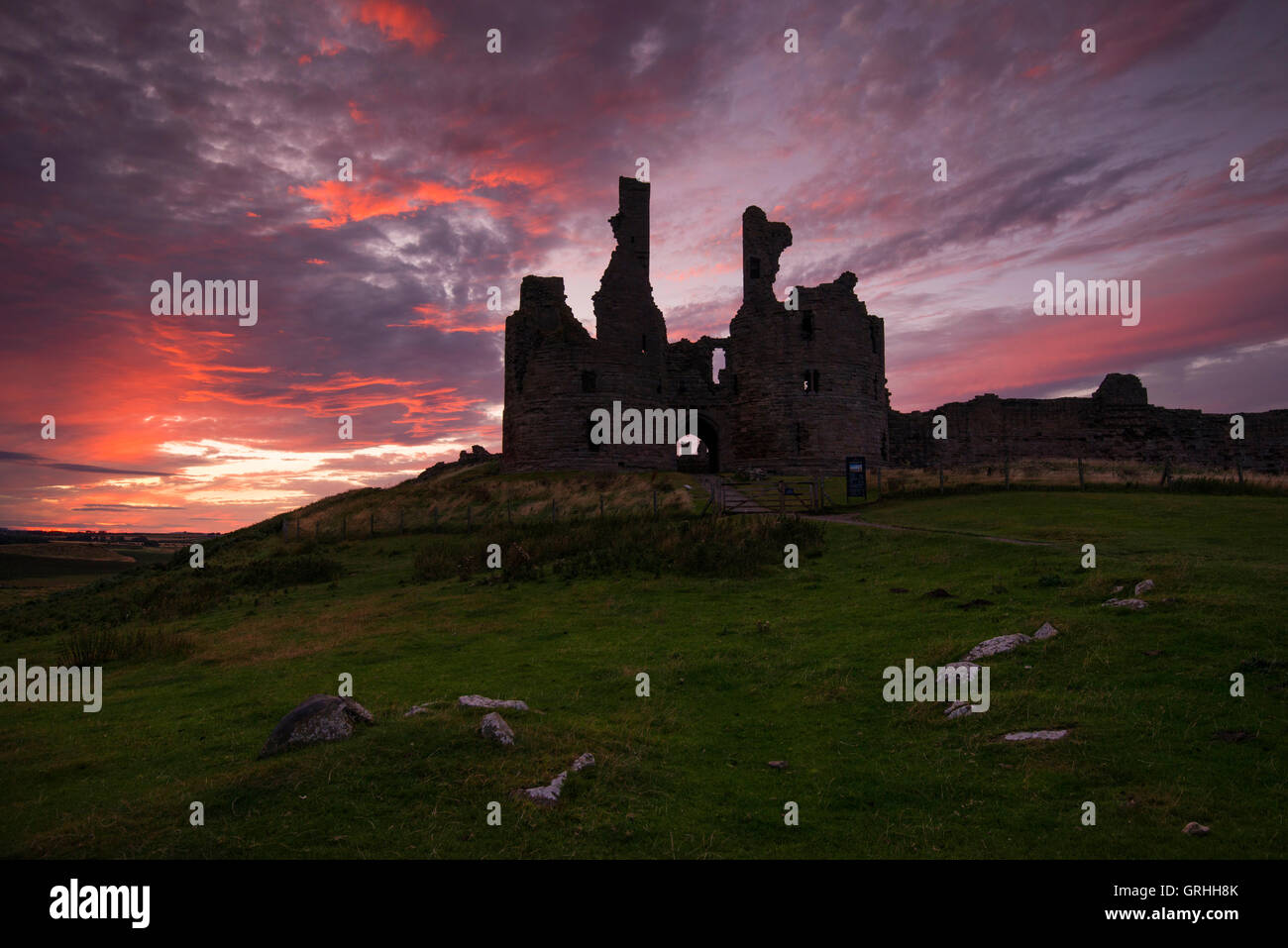 The foreboding ruins of Dunstanburgh Castle at sunset on the coast of Northumberland, England UK Stock Photo
