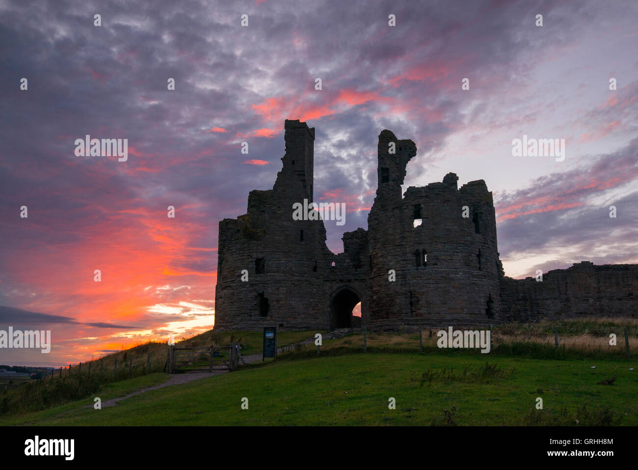 The foreboding ruins of Dunstanburgh Castle at sunset on the coast of Northumberland, England UK - Stock Image