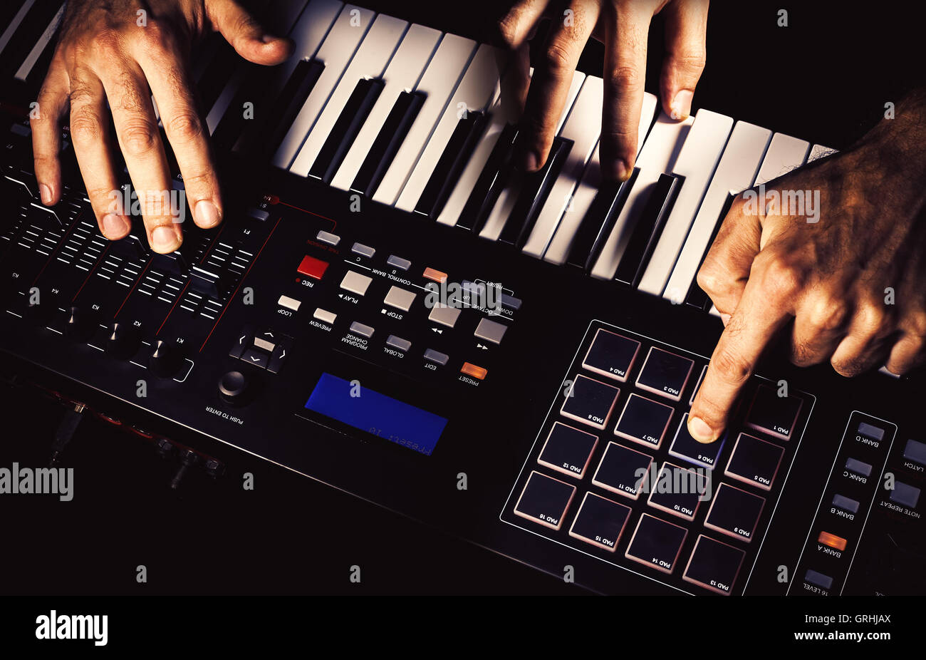 Details of a modern midi keyboard with male hands playing on it. - Stock Image