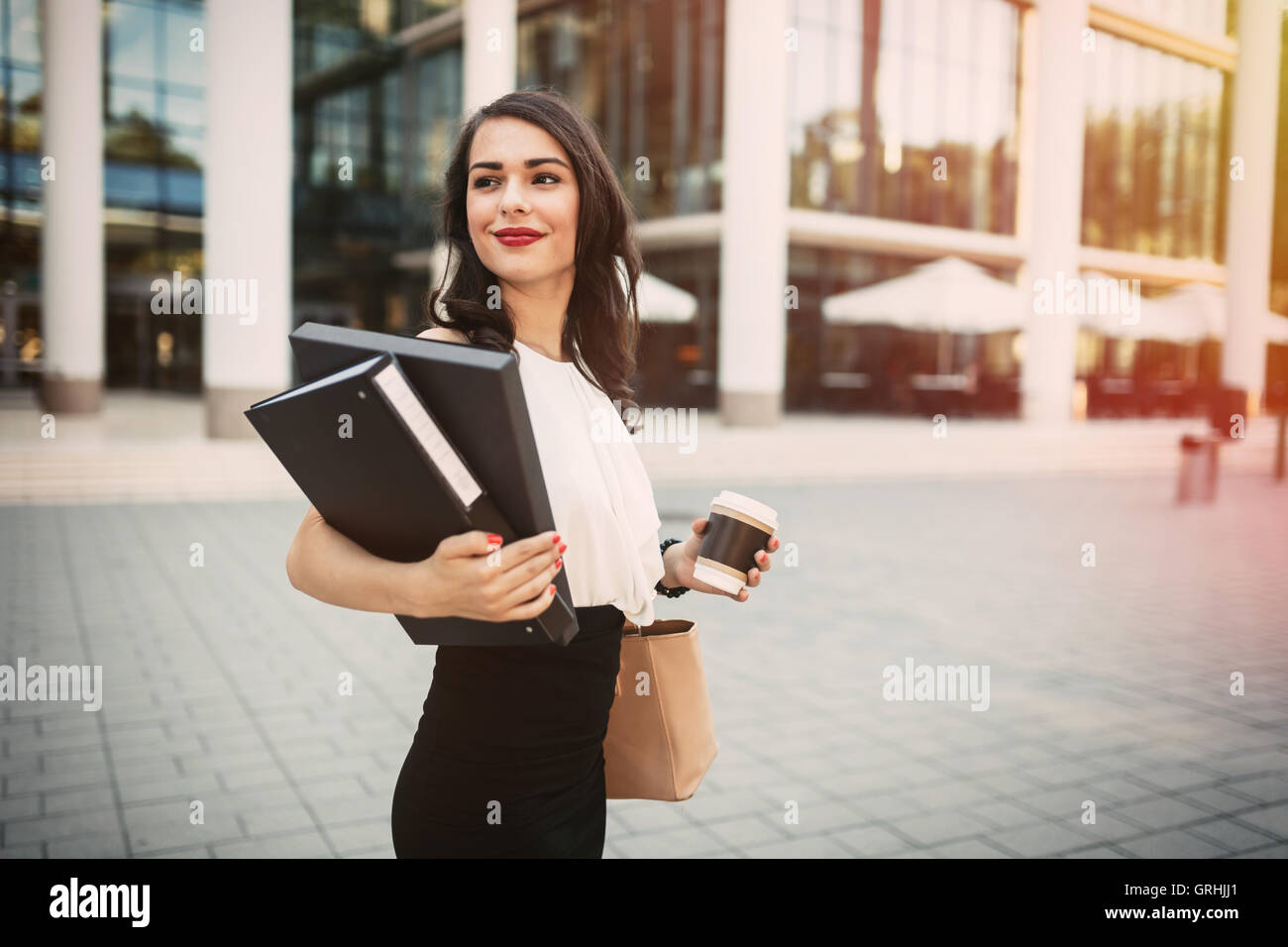 Businesswoman going to work with coffee in hand - Stock Image