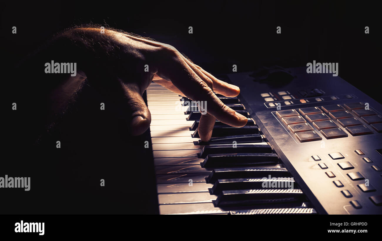 Playing a keyboard, left hand act, accentuated contrasts. - Stock Image