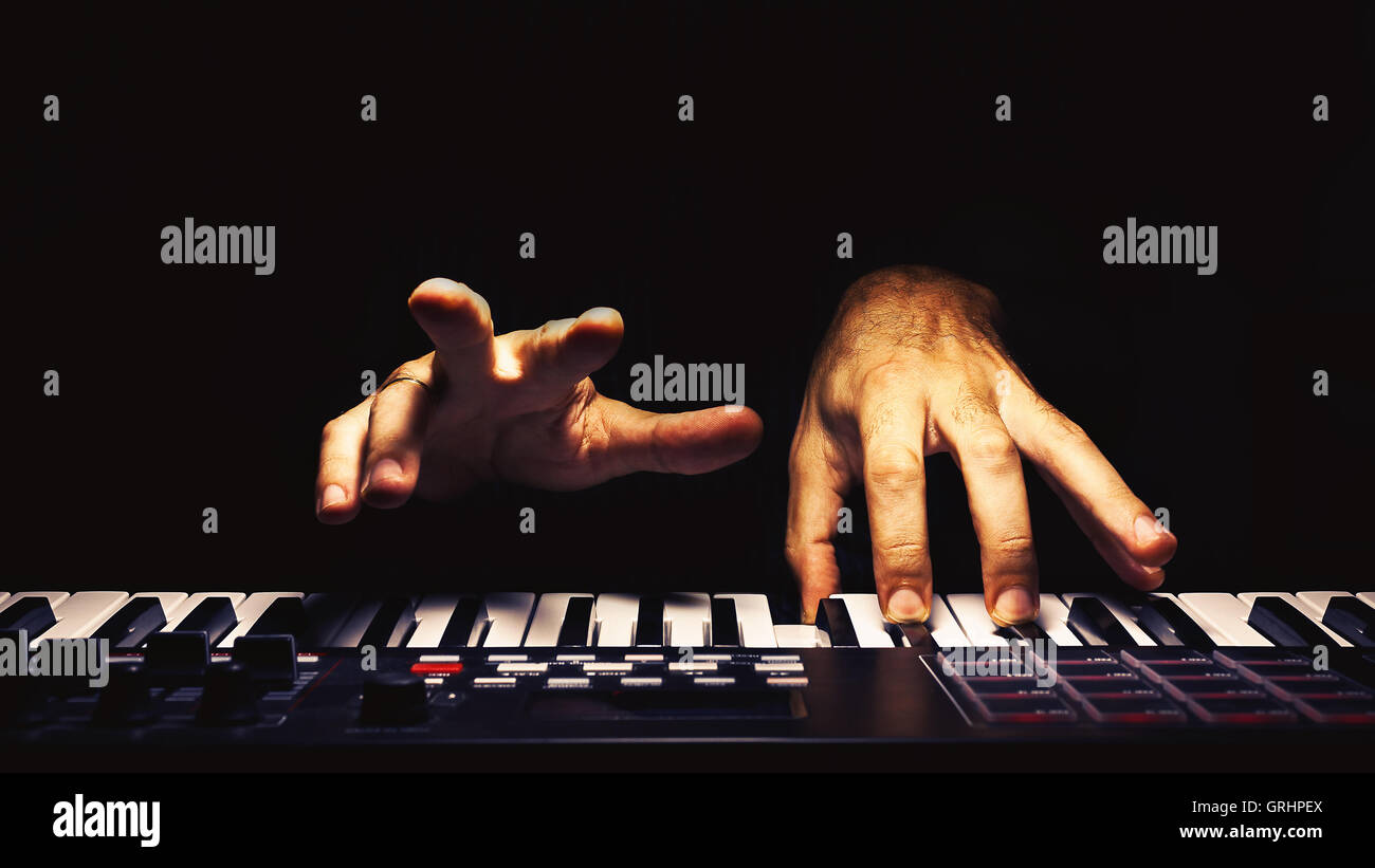 Playing a keyboard, illuminated and accentuated view on hands. - Stock Image
