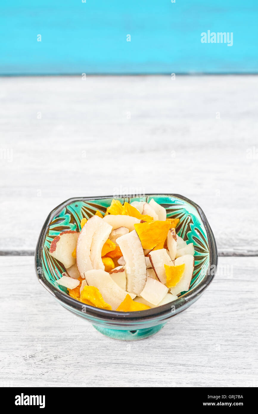 Dried coconut and mango slices in a green bowl on rustic table, space for text. - Stock Image