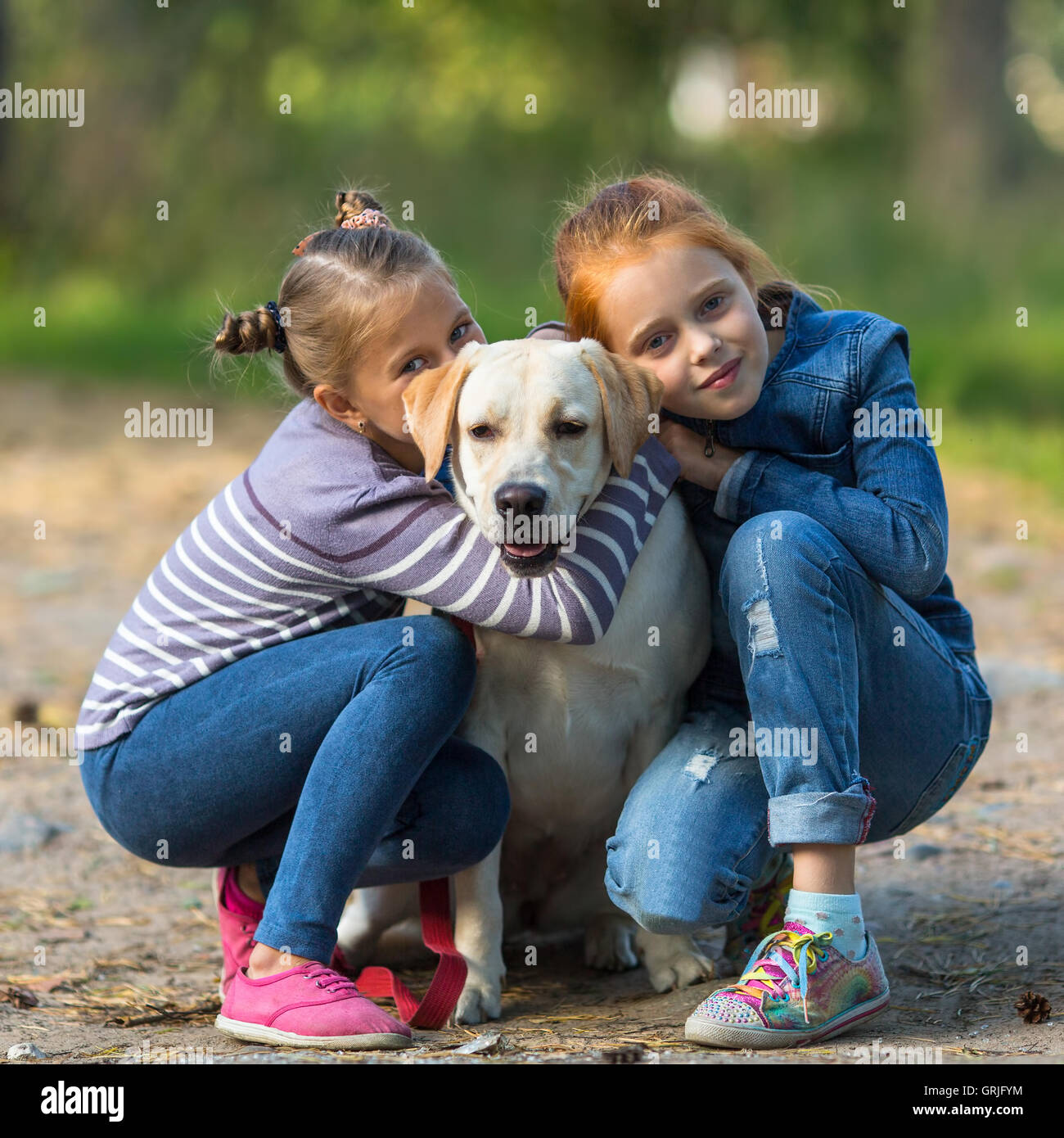 Two little girls with a dog. - Stock Image