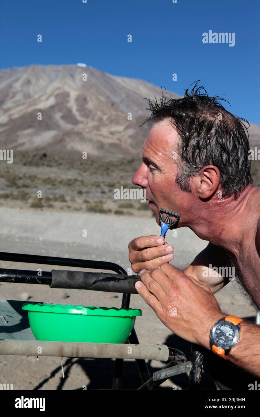 A man  (expedition leader) shaves with primitive sources on the slopes of Kilimanjaro. - Stock Image