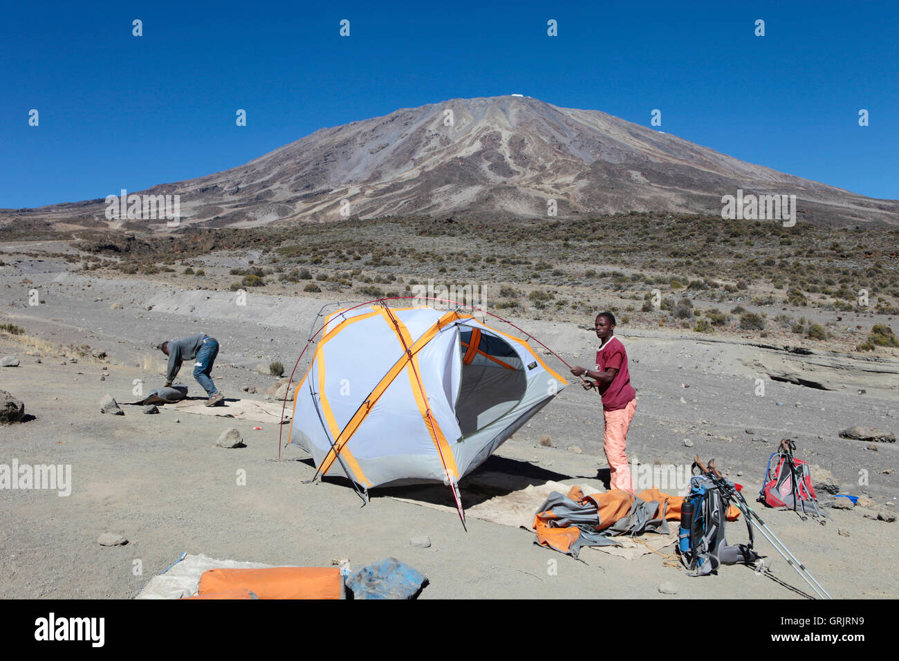 Two Tanzanian porters are setting up a tent for their western clients on the slopes of Kilimanjaro. - Stock Image