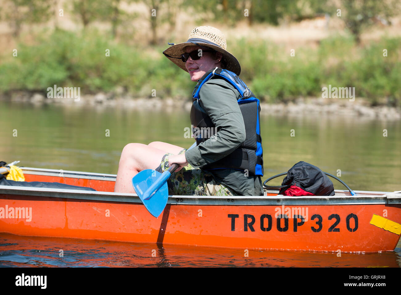 A Boy Scout paddles his canoe down the Clearwater River near Orofino, Idaho while traveling on the original Lewis - Stock Image