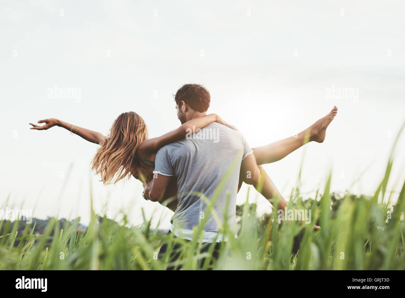 Rear view shot of man carrying woman in rural field. Couple enjoying outdoors on grass field. - Stock Image
