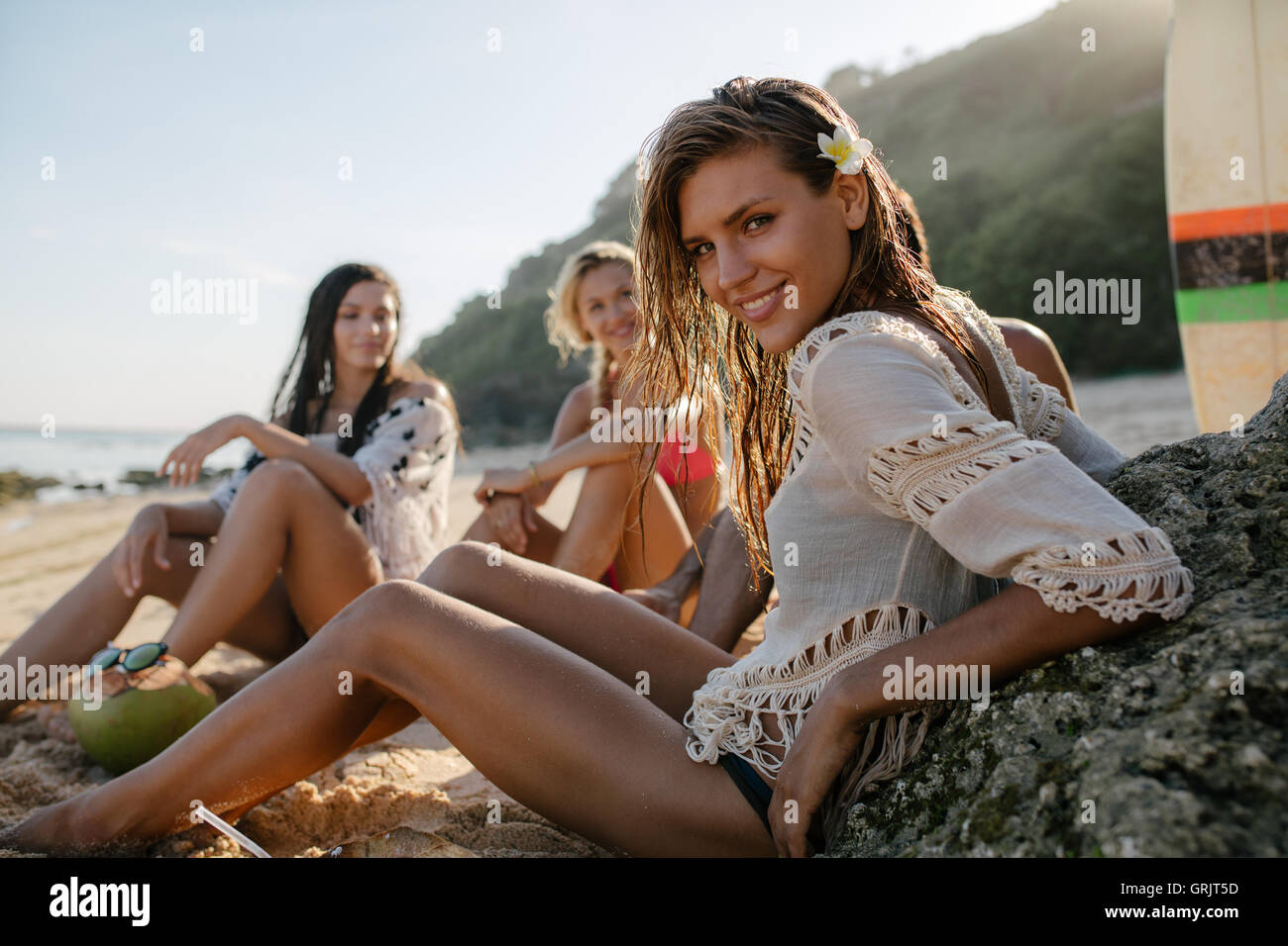 Happy young woman sitting on the beach with her friends in background. Group of friends enjoying on beach holiday. - Stock Image