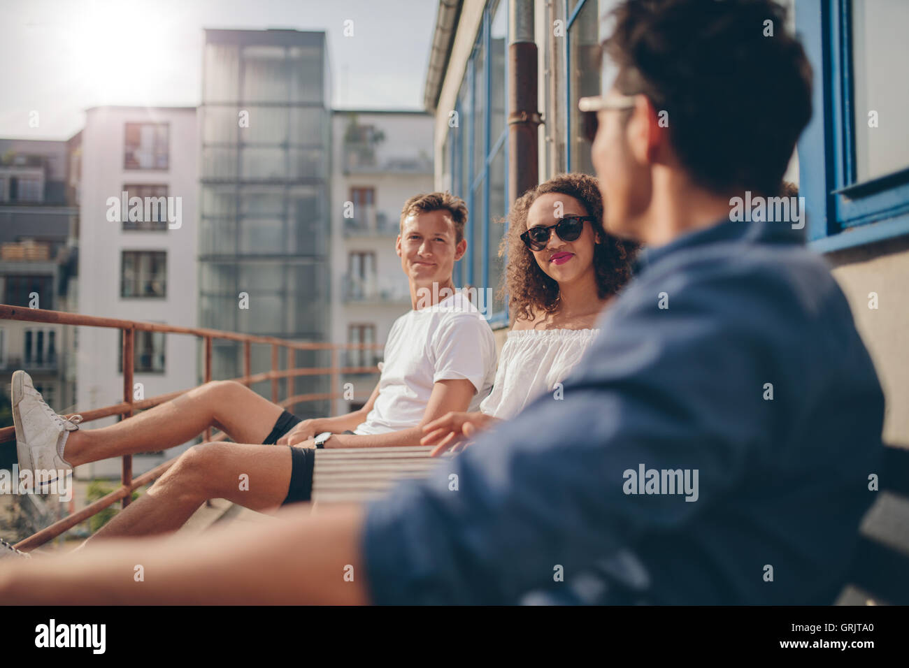 Shot of young woman sitting with her friends at outdoor cafe. Group of young people relaxing in a balcony. - Stock Image