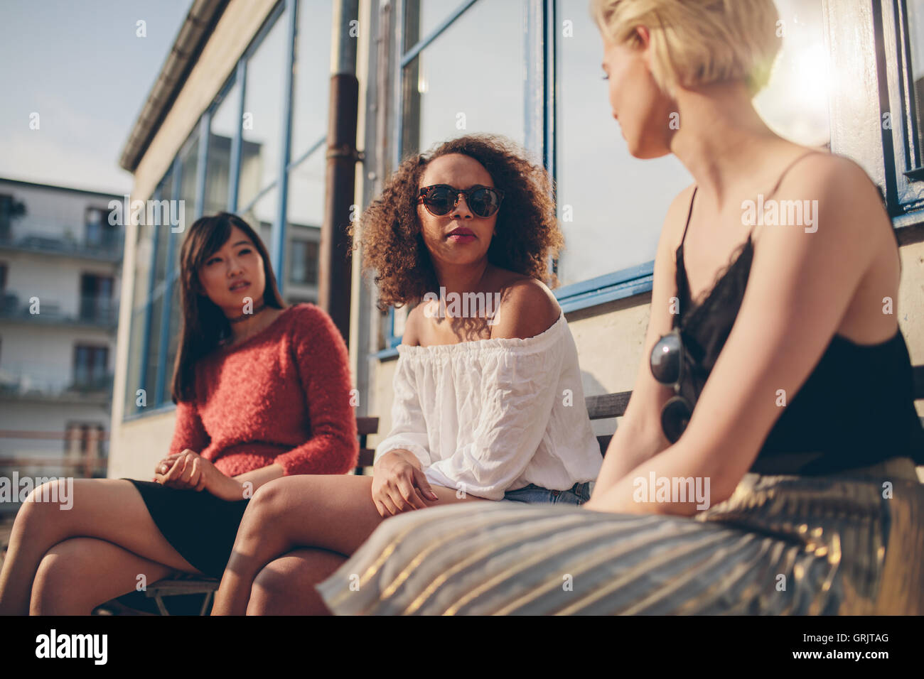 Three young female friends meeting outdoors. Multiracial group of young women sitting outdoors and chatting. - Stock Image