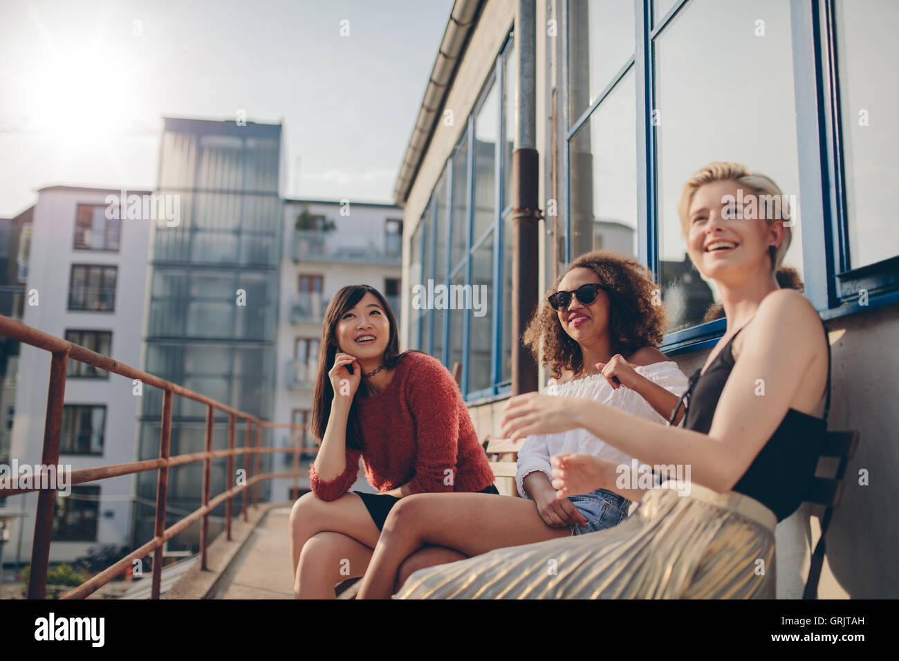 Happy three young female friends sitting in balcony and smiling. Women relaxing outdoors in terrace. - Stock Image