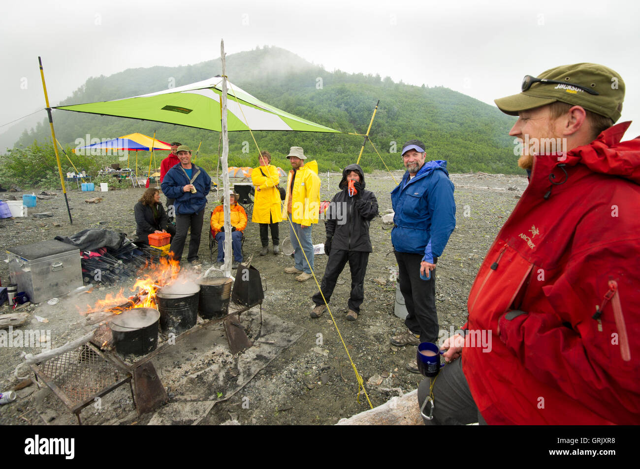 Rafters relaxing around the campfire on a rainy day along the shores of Alsek Lake, Alsek River - Stock Image