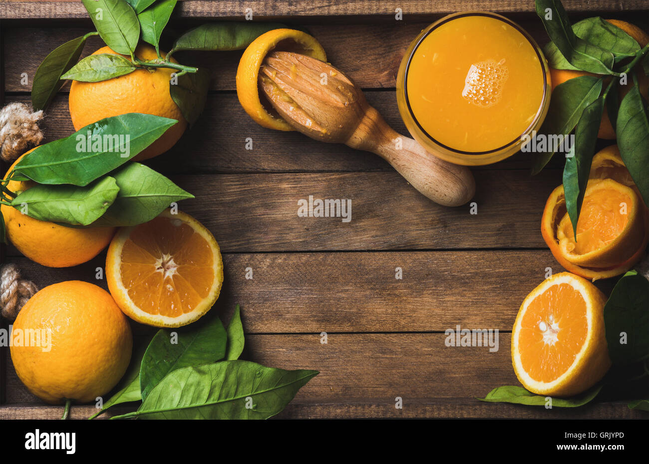 Glass of freshly squeezed juice and fresh oranges - Stock Image