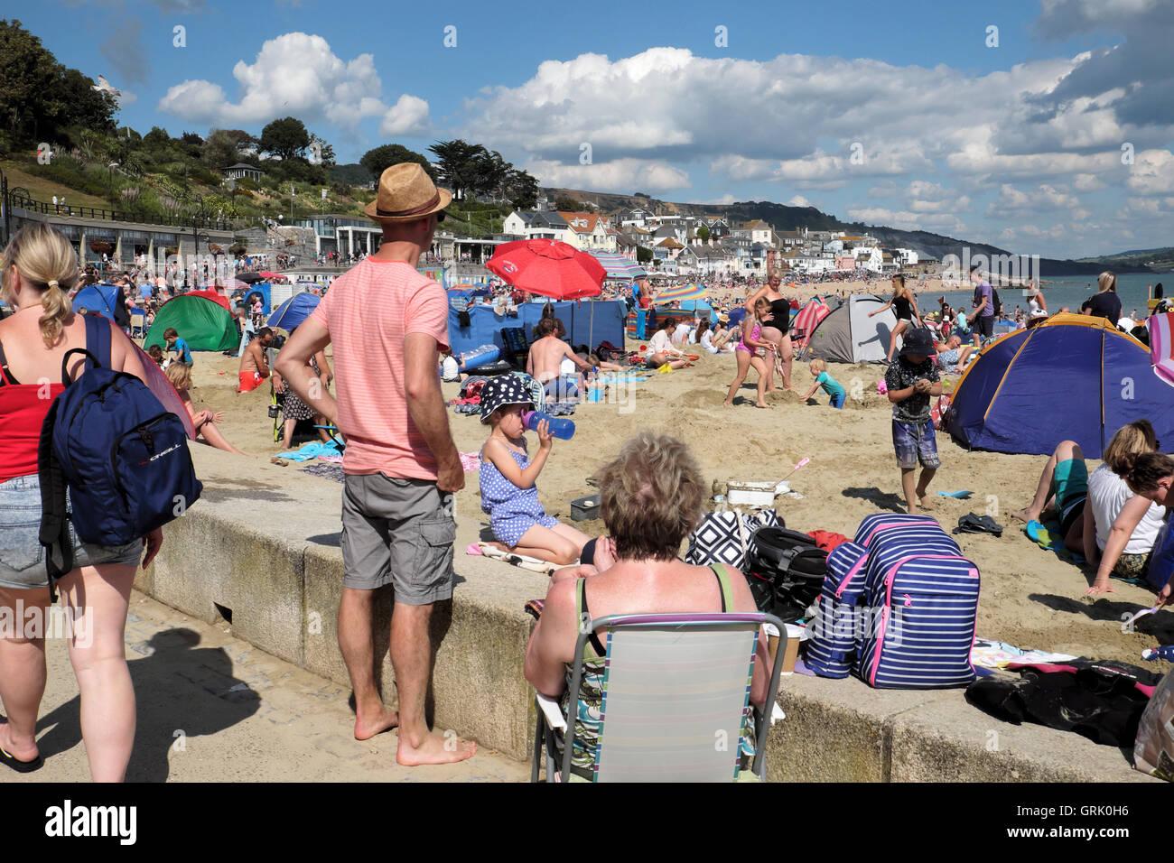 People in summer on the beach at Lyme Regis, Dorset, England UK  KATHY DEWITT - Stock Image