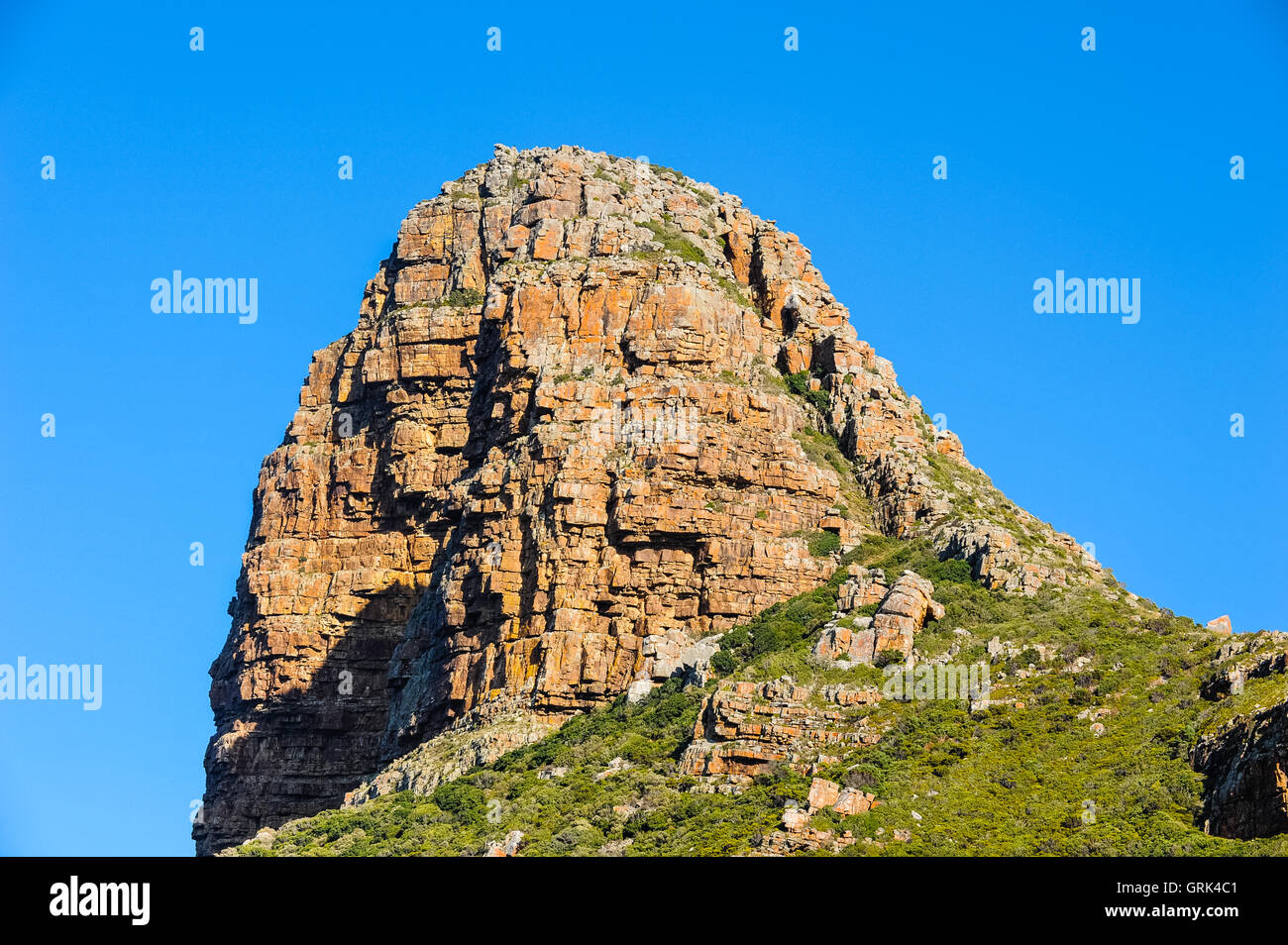 Hout Bay a coastal suburb of Cape Town, South Africa. This mountain is called the Sentinel. - Stock Image