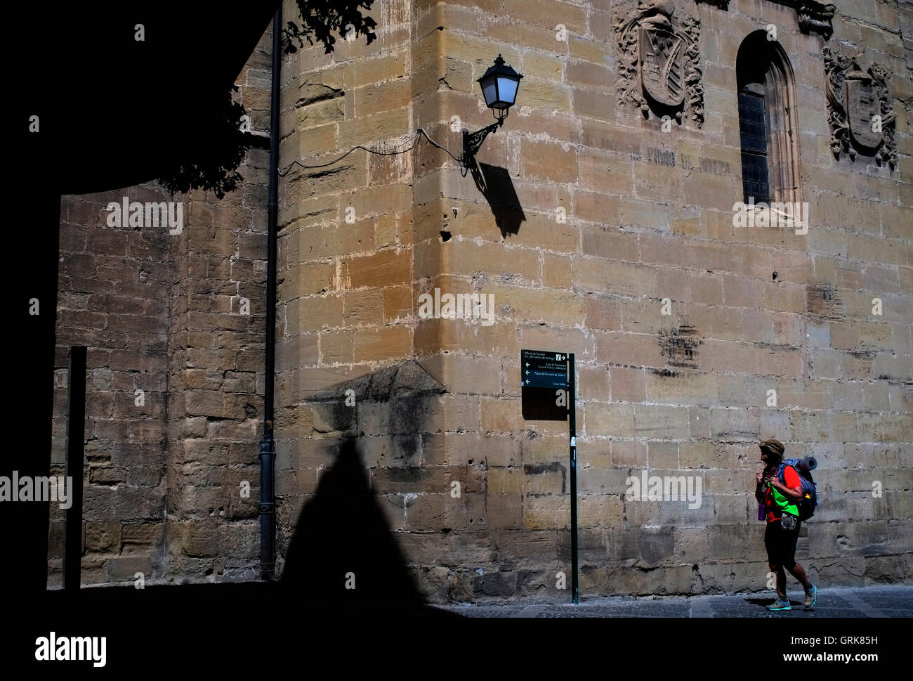 A modern day pilgrim passes the cathedral in Santo Domingo dela Calzada, Spain August 25, 2016. Copyright photograph Stock Photo