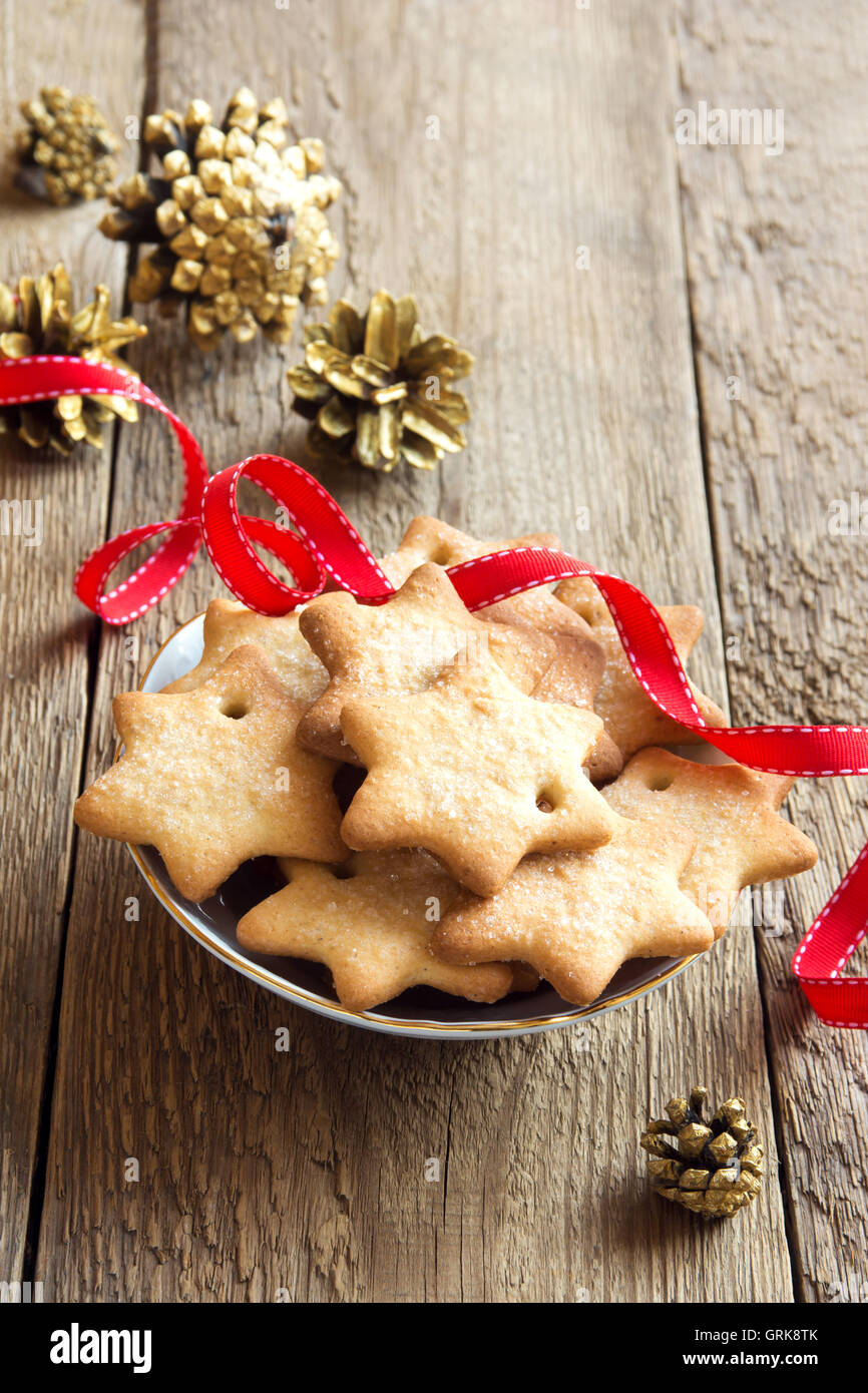 Gingerbread Christmas cookies on rustic wooden table with golden pine cones and red ribbon for winter holidays - Stock Image