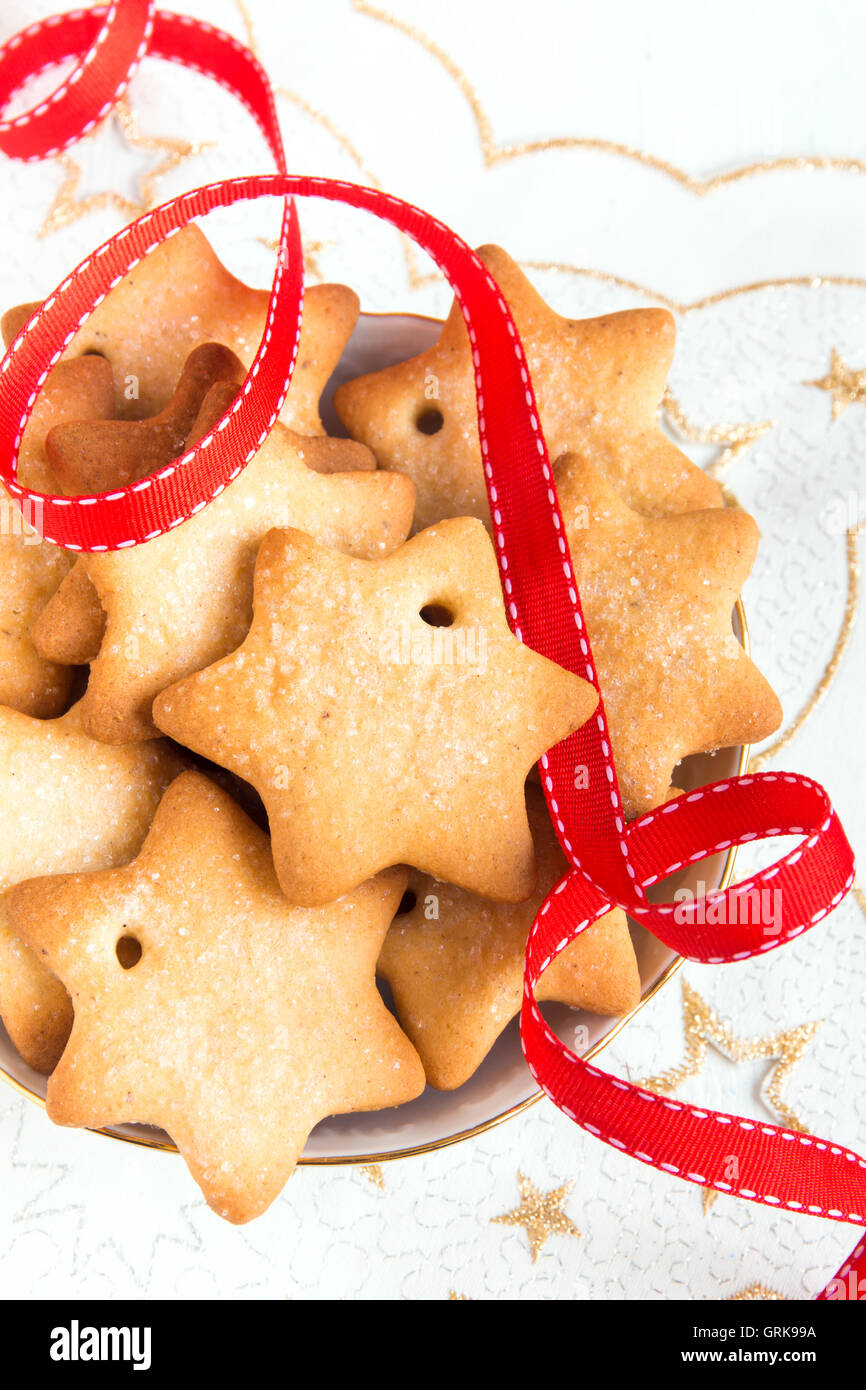 Gingerbread Christmas cookies on white napkin with stars and red ribbon for winter holidays - Stock Image