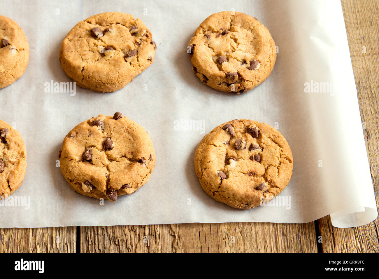 Chocolate chip cookies on baking paper and rustic wooden table Stock Photo