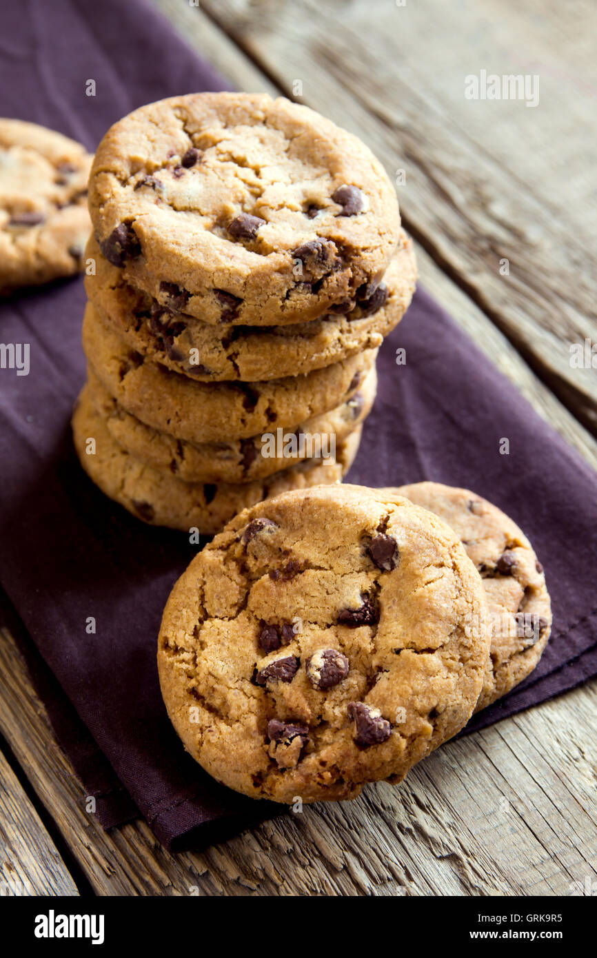 Chocolate chip cookies on brown napkin and rustic wooden table - Stock Image