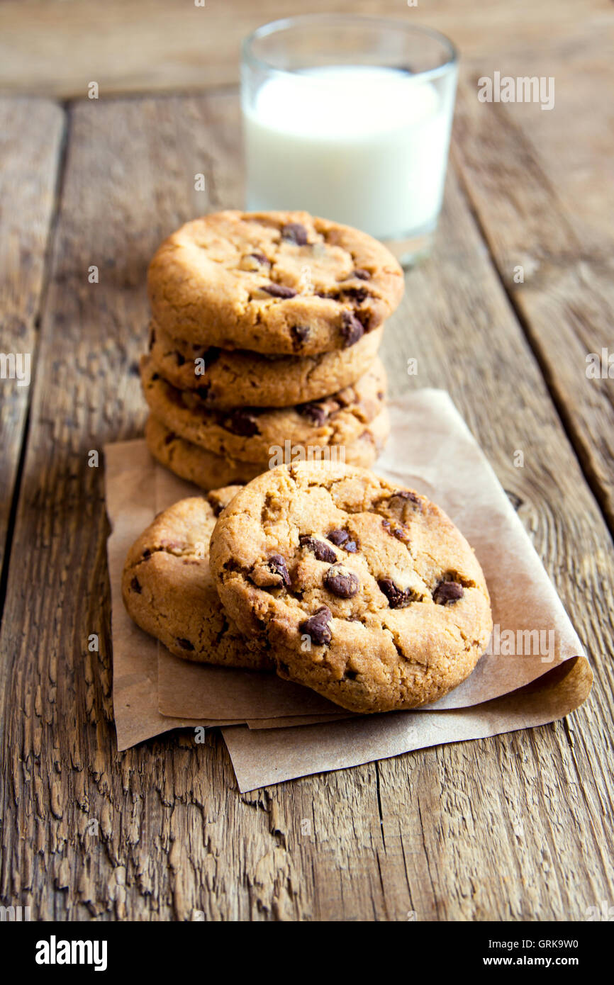 Chocolate chip cookies with milk on paper and rustic wooden table - Stock Image