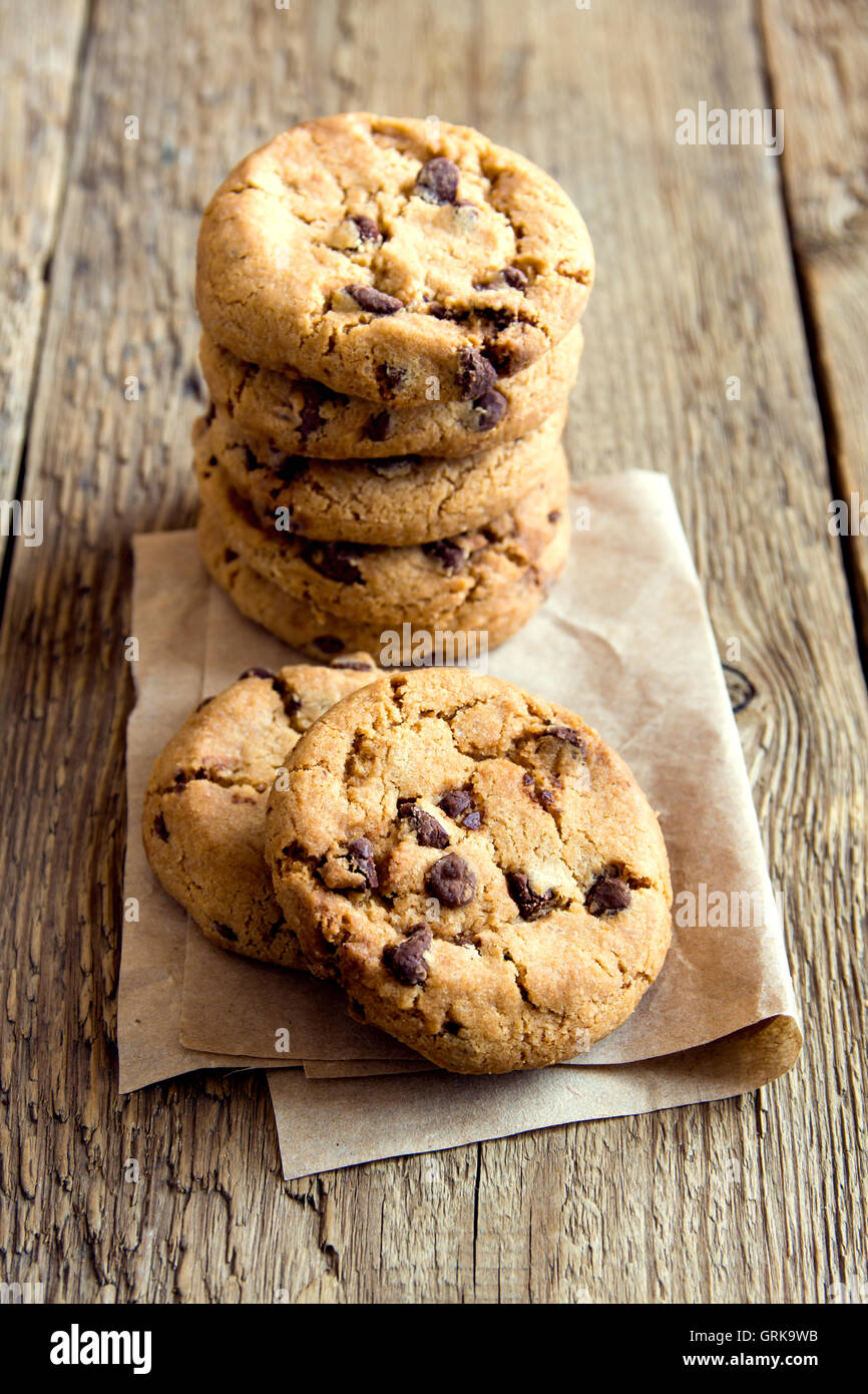 Chocolate chip cookies on paper and rustic wooden table - Stock Image