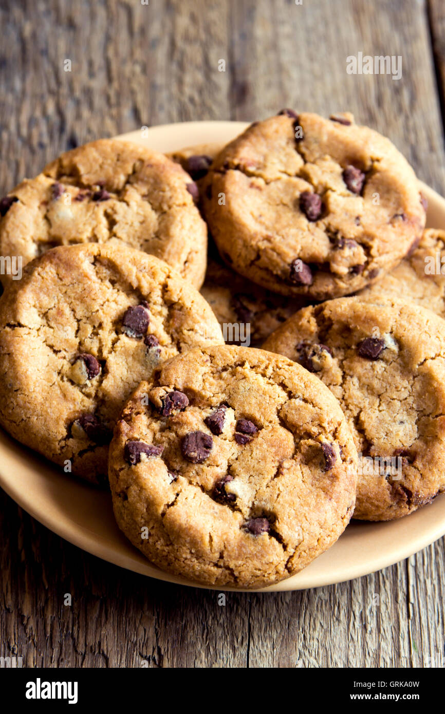 Chocolate chip cookies on plate and rustic wooden table - Stock Image