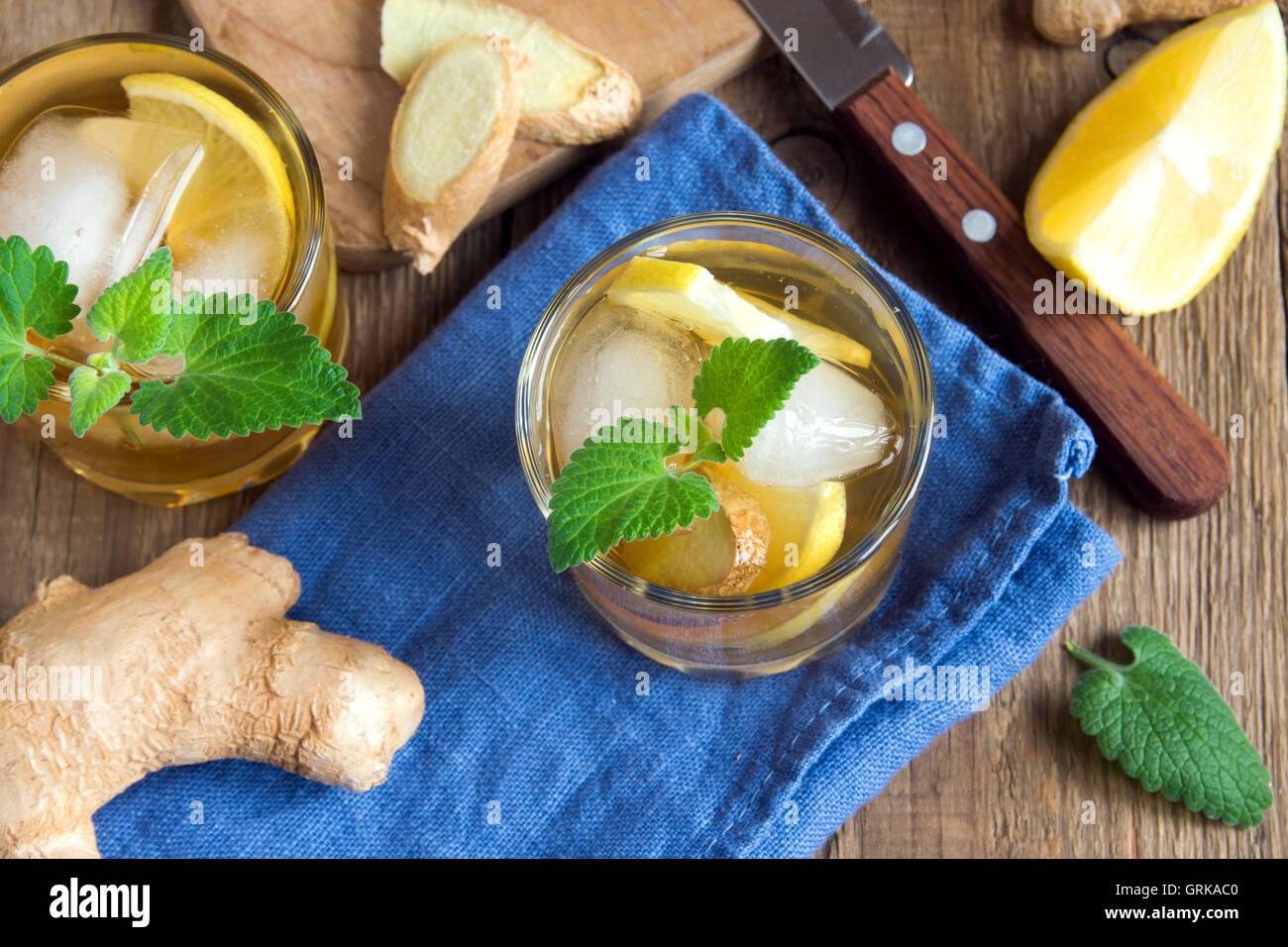 Ginger ale soda with lemon, mint, ginger and ice over rustic wooden background - Stock Image